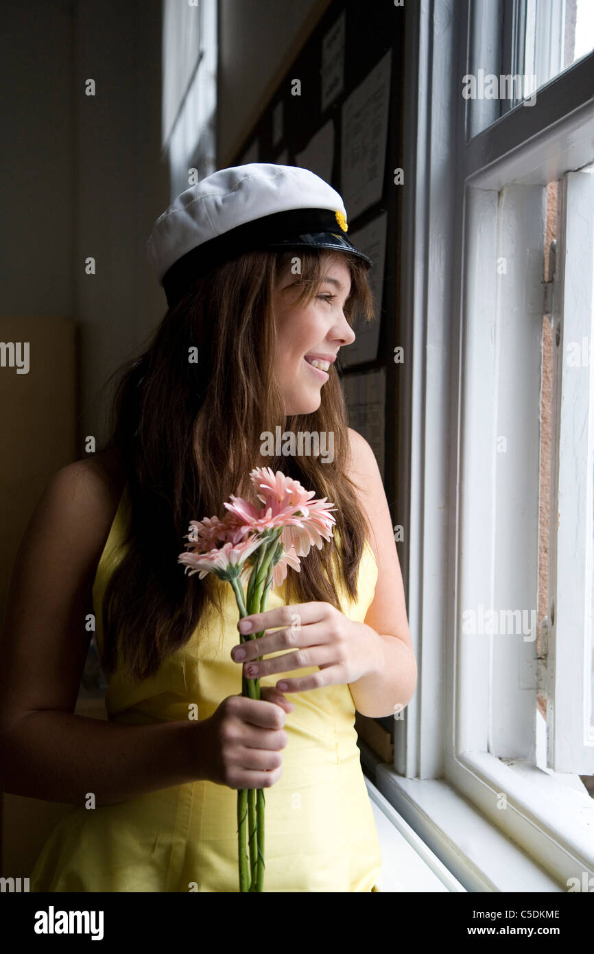 Smiling female student in graduation hat with flowers looking through  window - Stock Image 6af7f7d11a6f