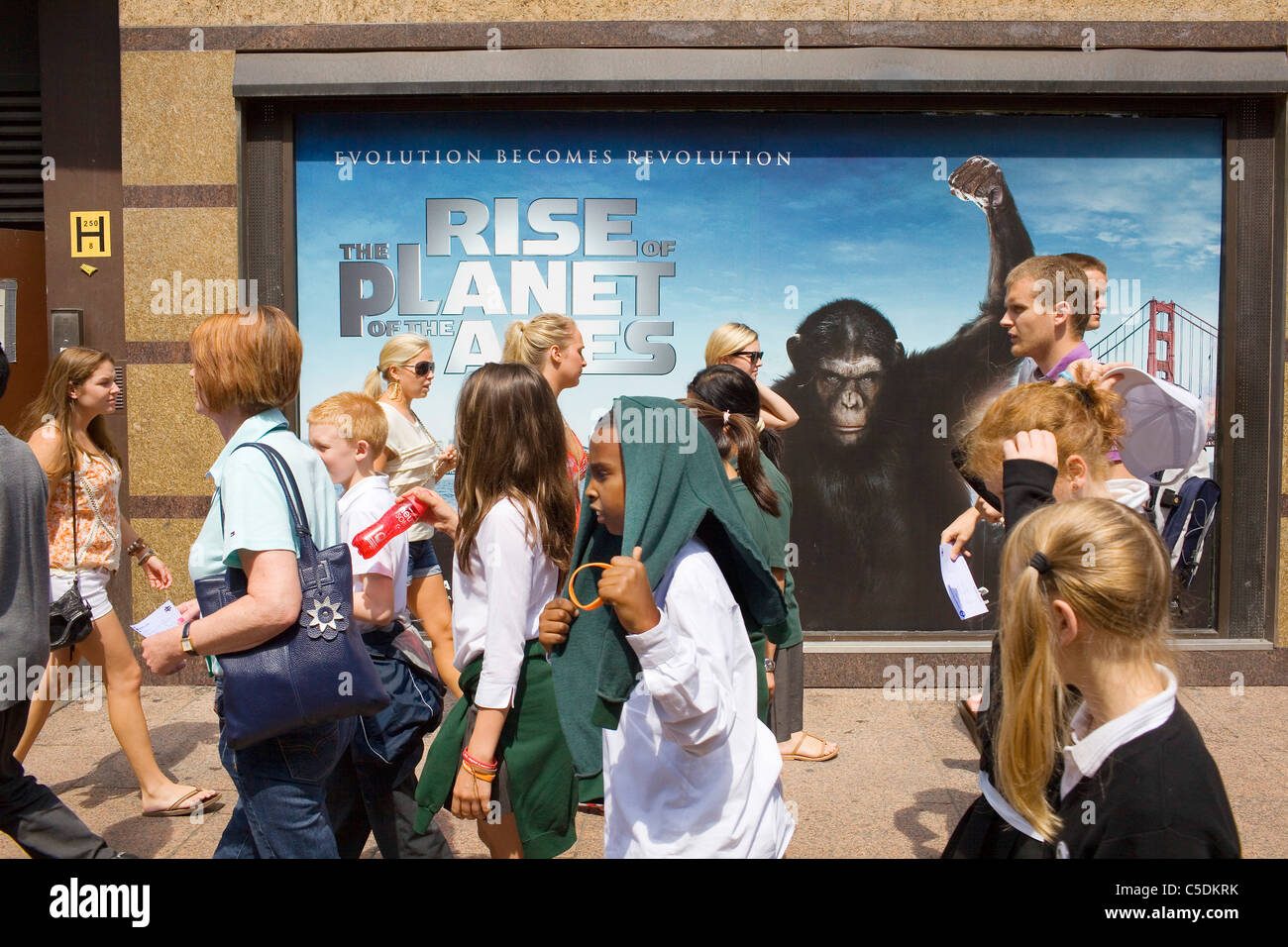 Visitors to London's Leicester Square walk past a poster with an ape on. - Stock Image