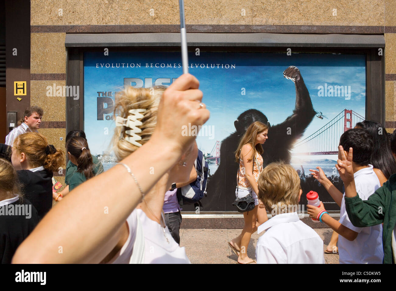 Crowds in Leicester Square walk past a poster with an Ape on. - Stock Image