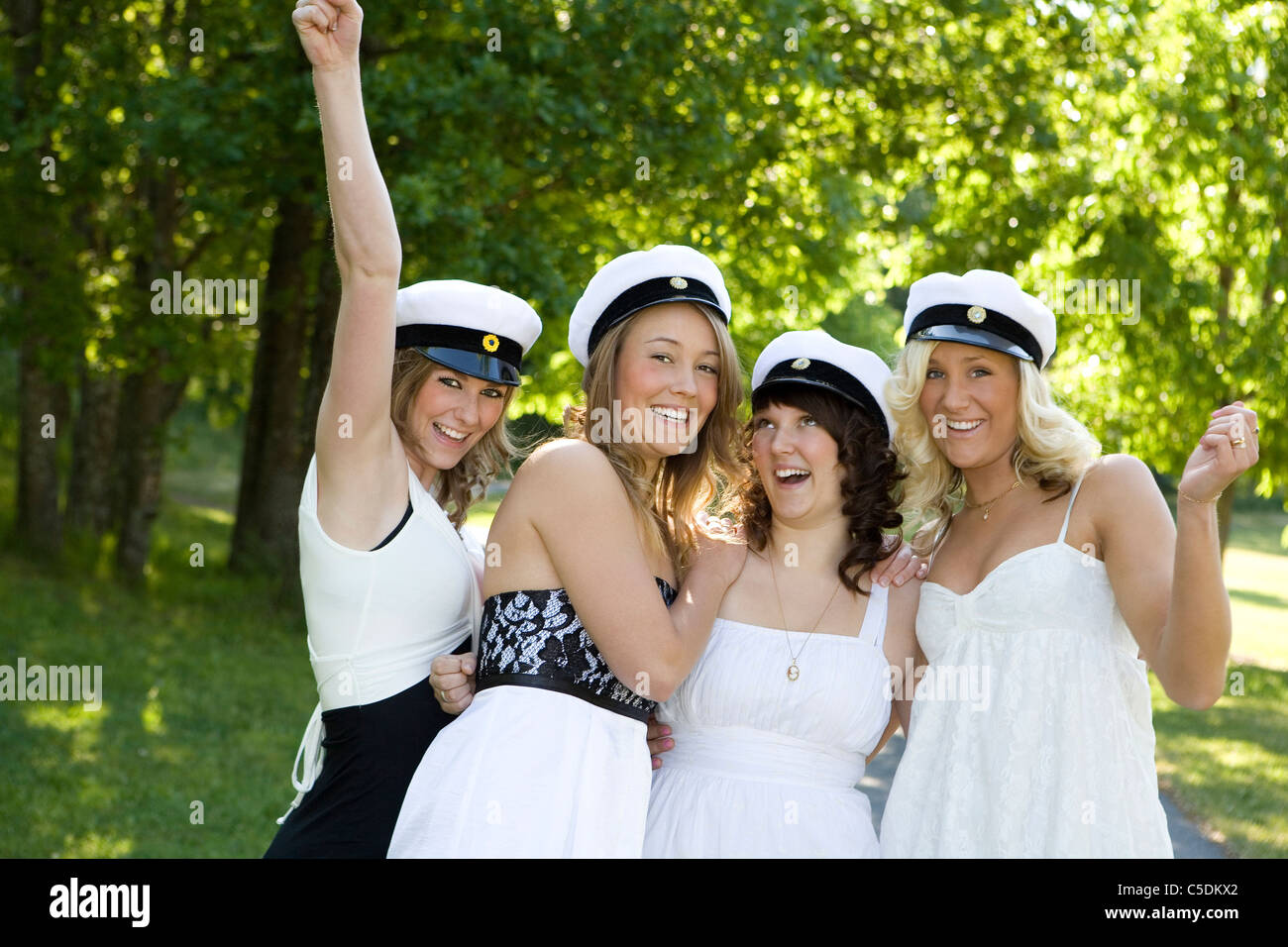 Portrait of four happy female students in graduation hats against blurred trees - Stock Image