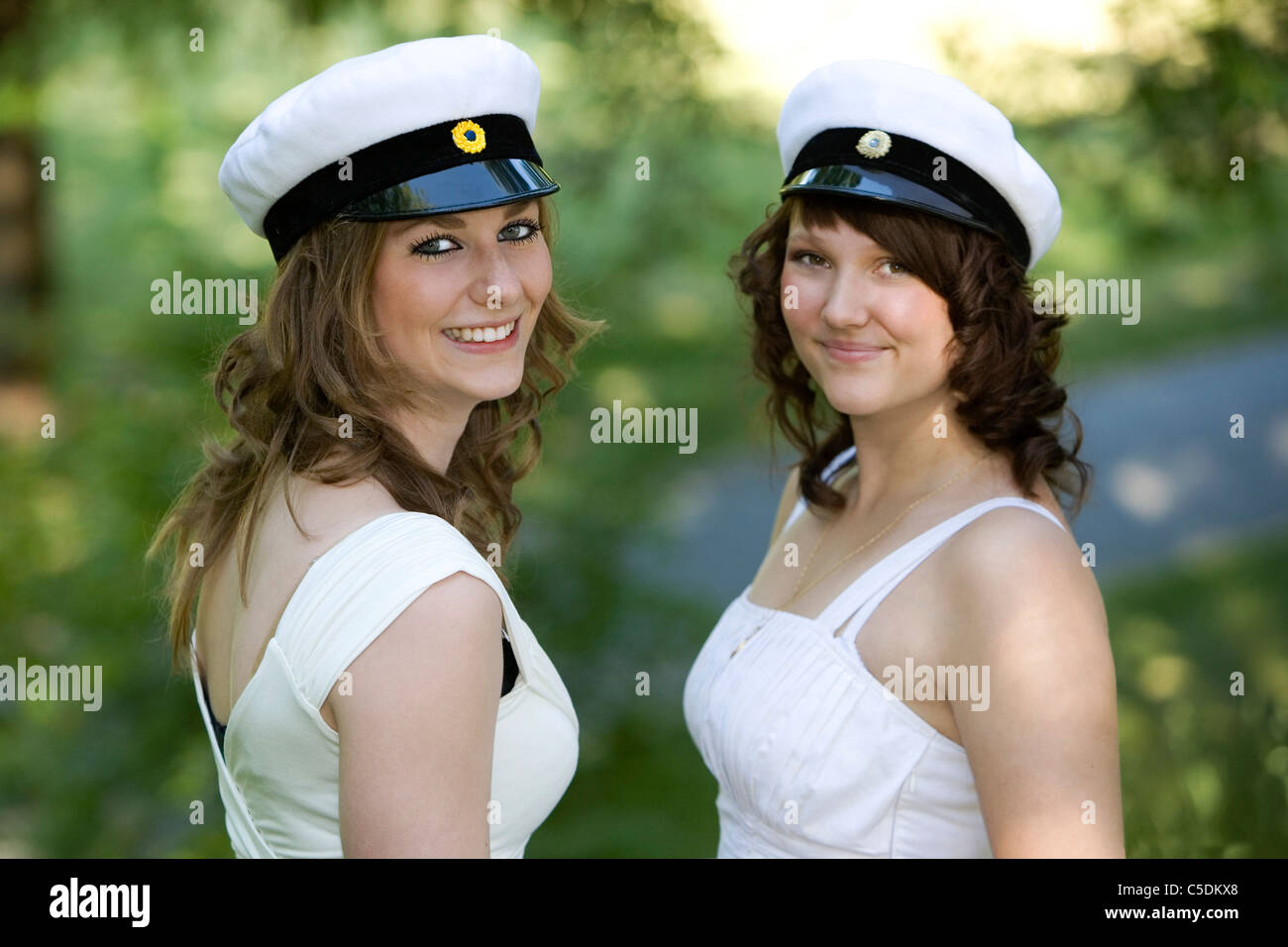 Portrait of two happy female students in graduation hats against blurred green background - Stock Image