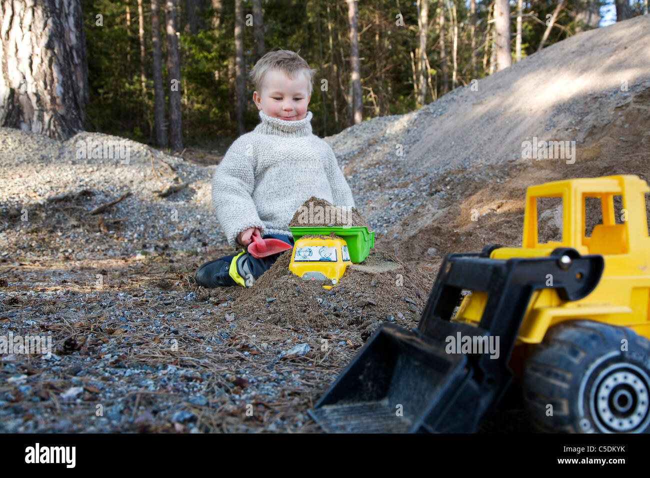 Little boy sitting in sandbox with cropped toy backhoe in foreground Stock Photo
