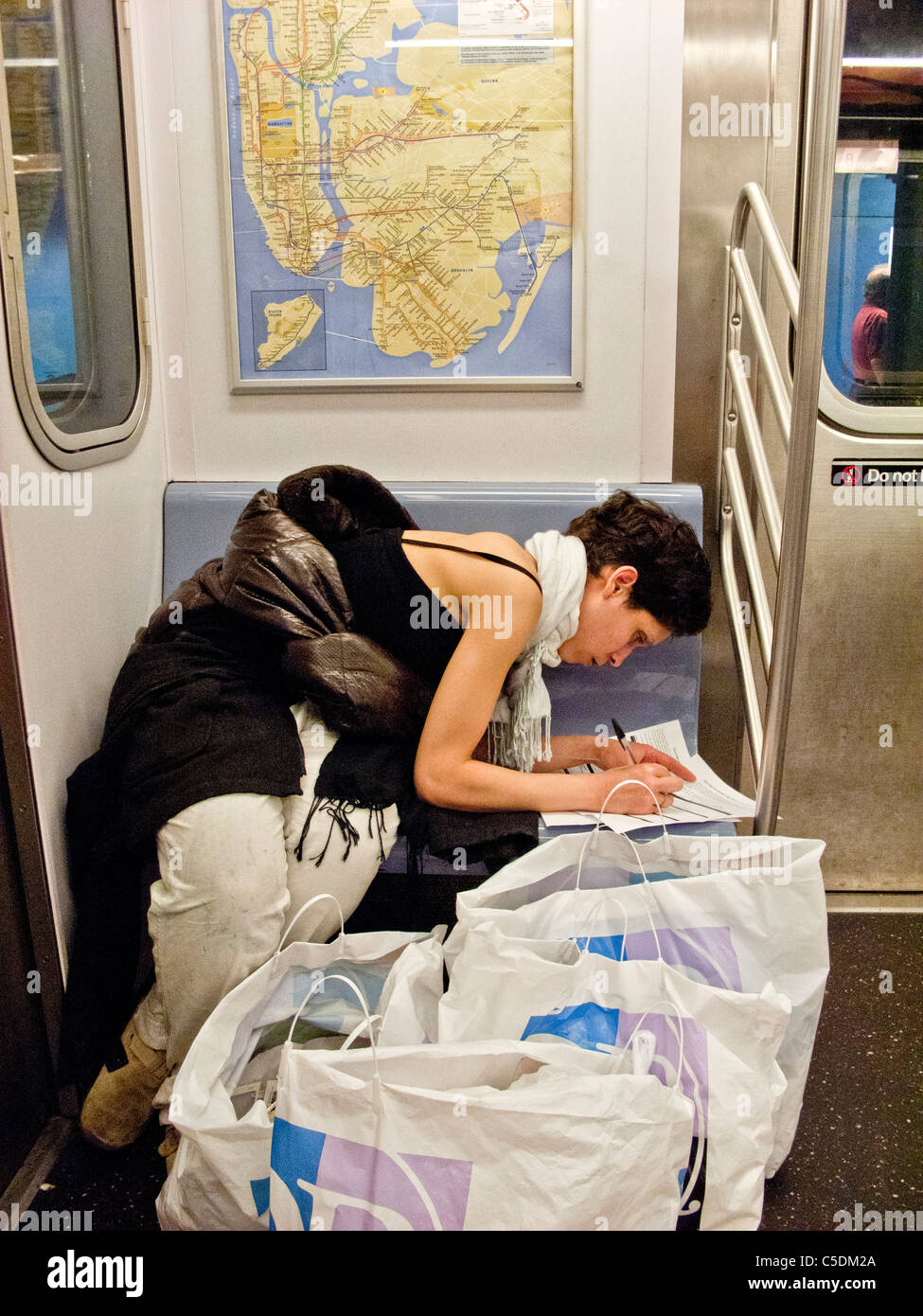Surrounded by shopping bags, a young woman fills out a job application while riding on the subway in New York City. - Stock Image