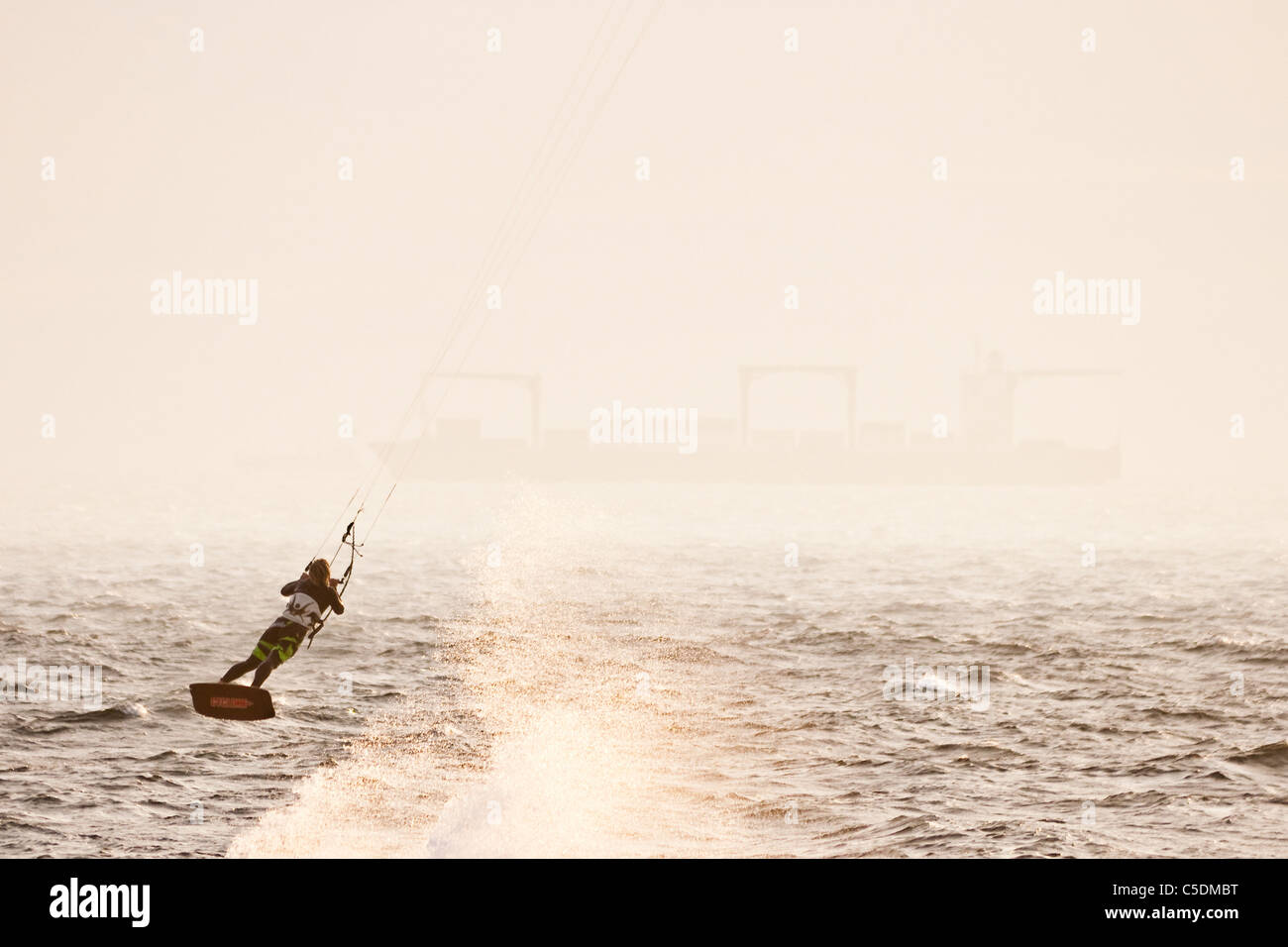 Kiteboarder launches off the crest of a wave, sending sea spray flying. - Stock Image