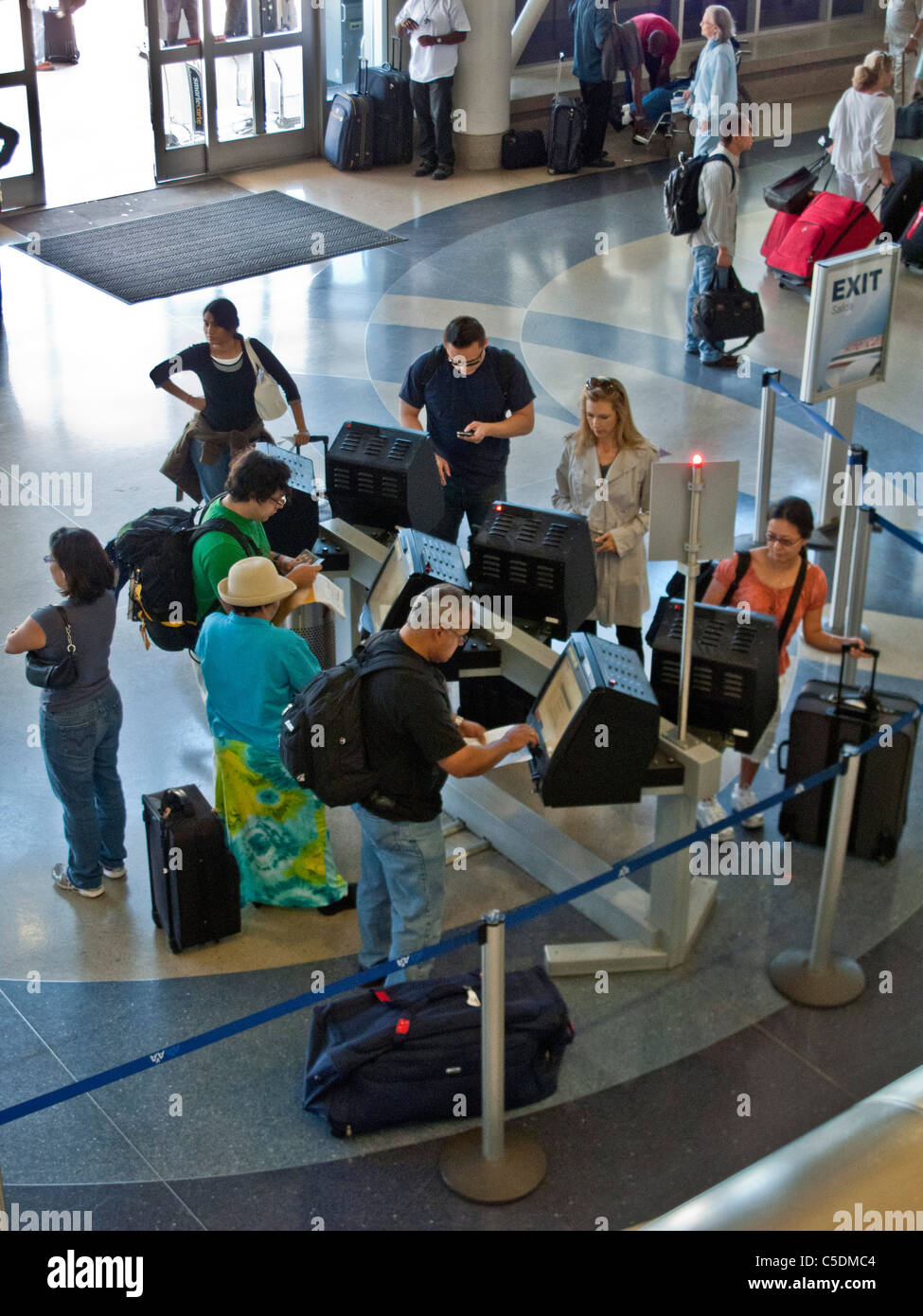 Airline passengers obtain boarding passes at computer terminals at Los Angeles International Airport, also known - Stock Image