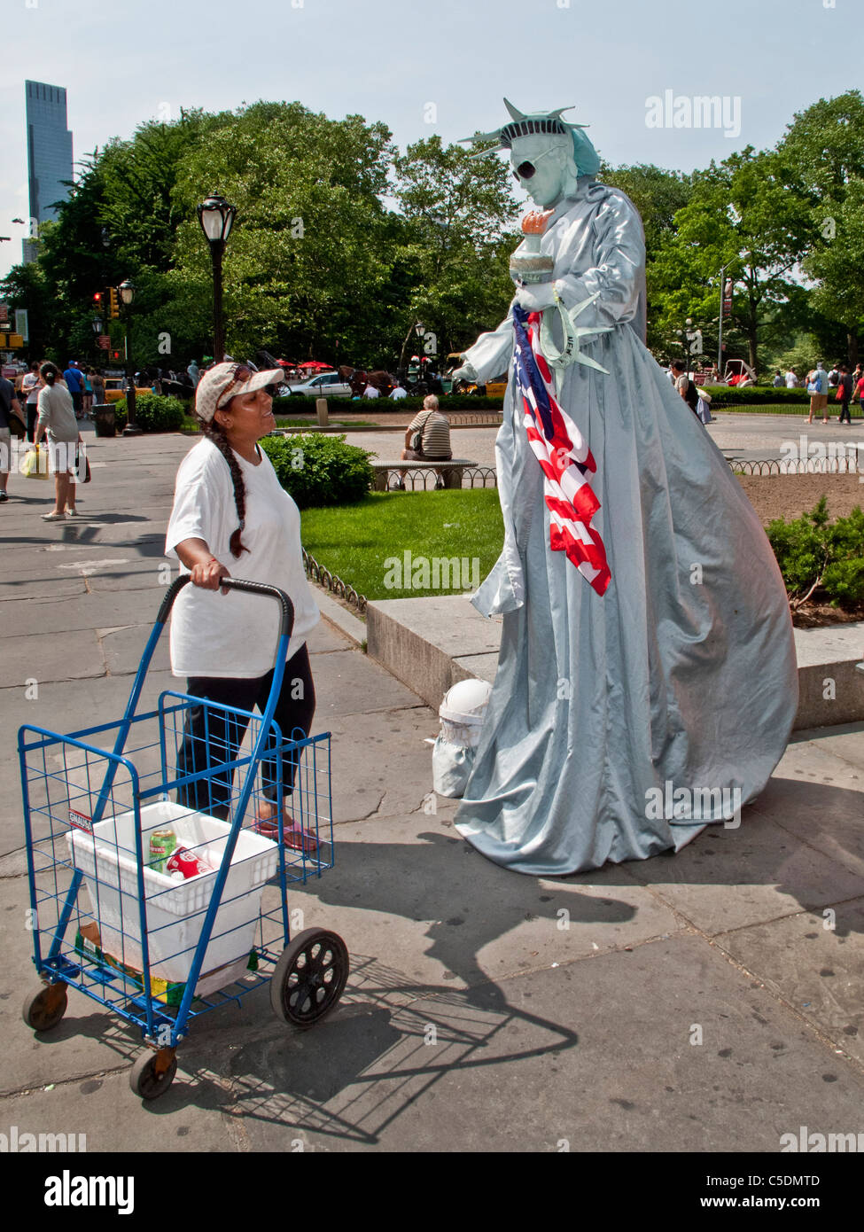 A mime dressed as the Statue of Liberty talks with a passerby on Fifth Avenue, Manhattan, New York City. Note sunglasses. - Stock Image