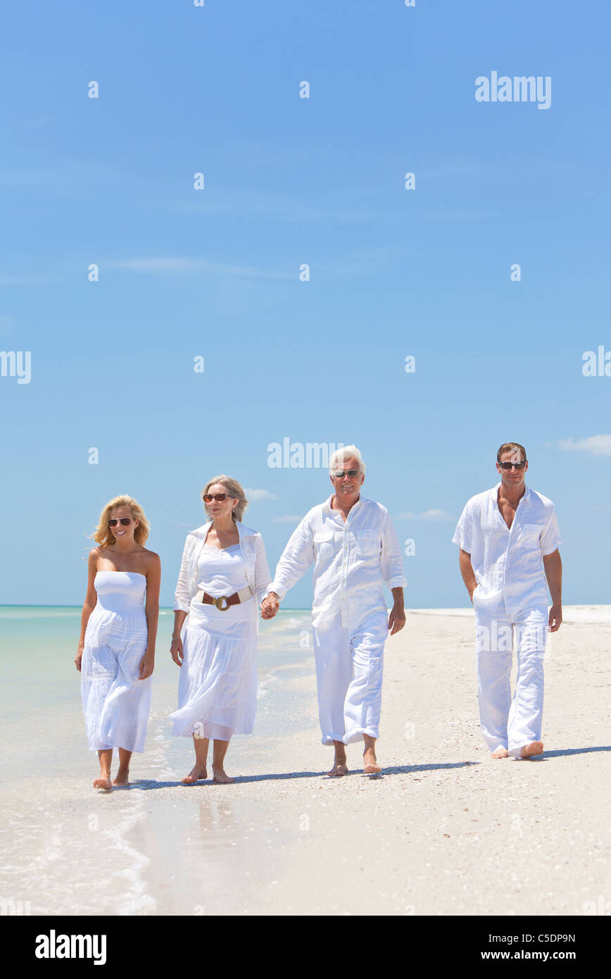 Four people, two seniors, couples or family generations, holding hands, having fun and walking on a tropical beach - Stock Image