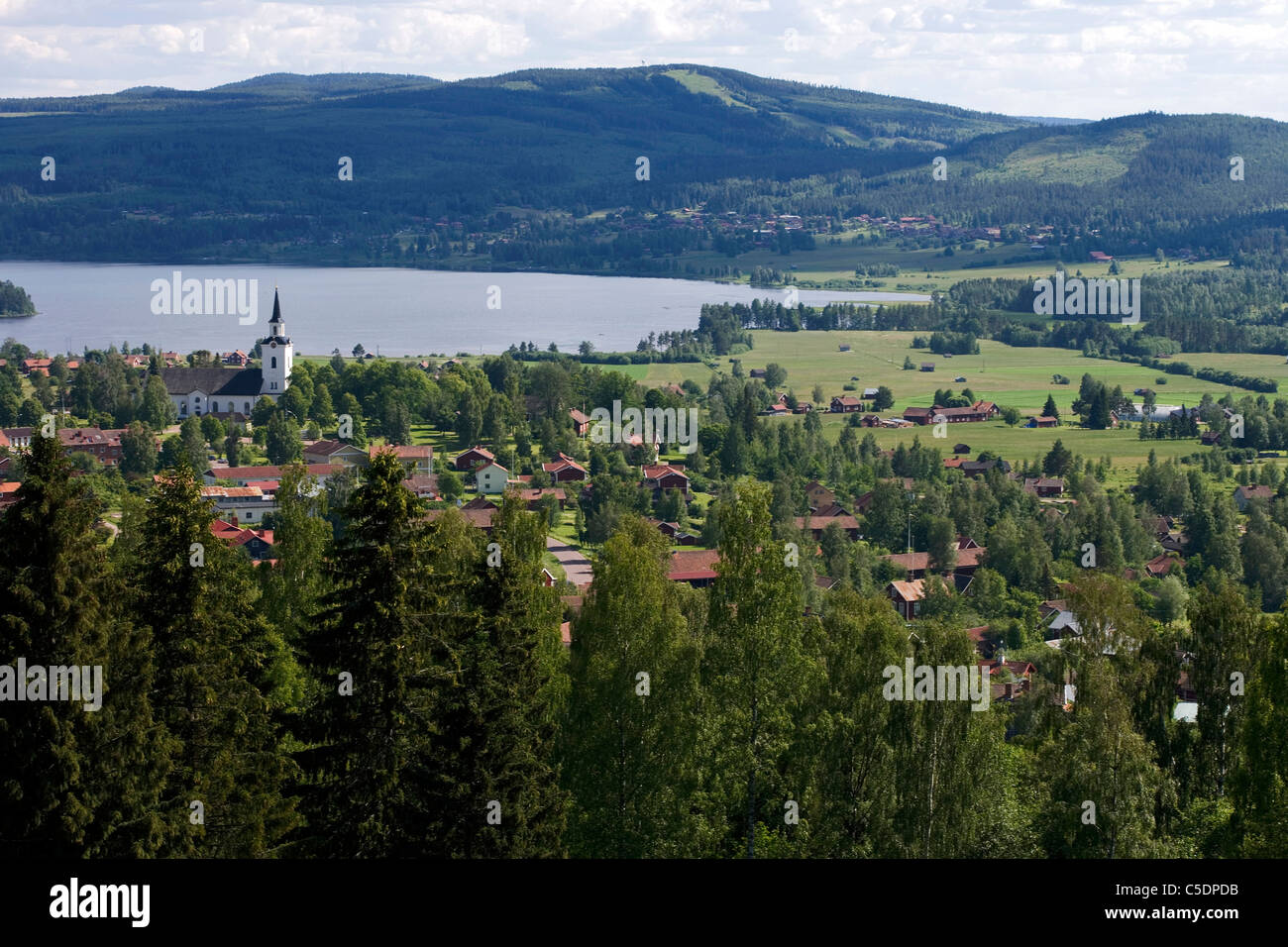 Overview of trees with houses by peaceful lake and mountains in background at Dalarna, Sweden - Stock Image