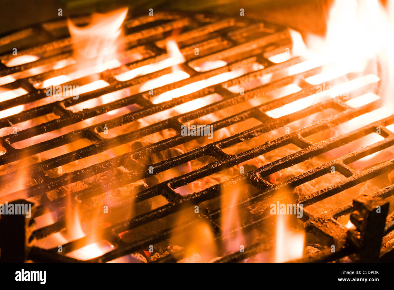 Closeup of charcoal burning under a barbecue grill - Stock Image