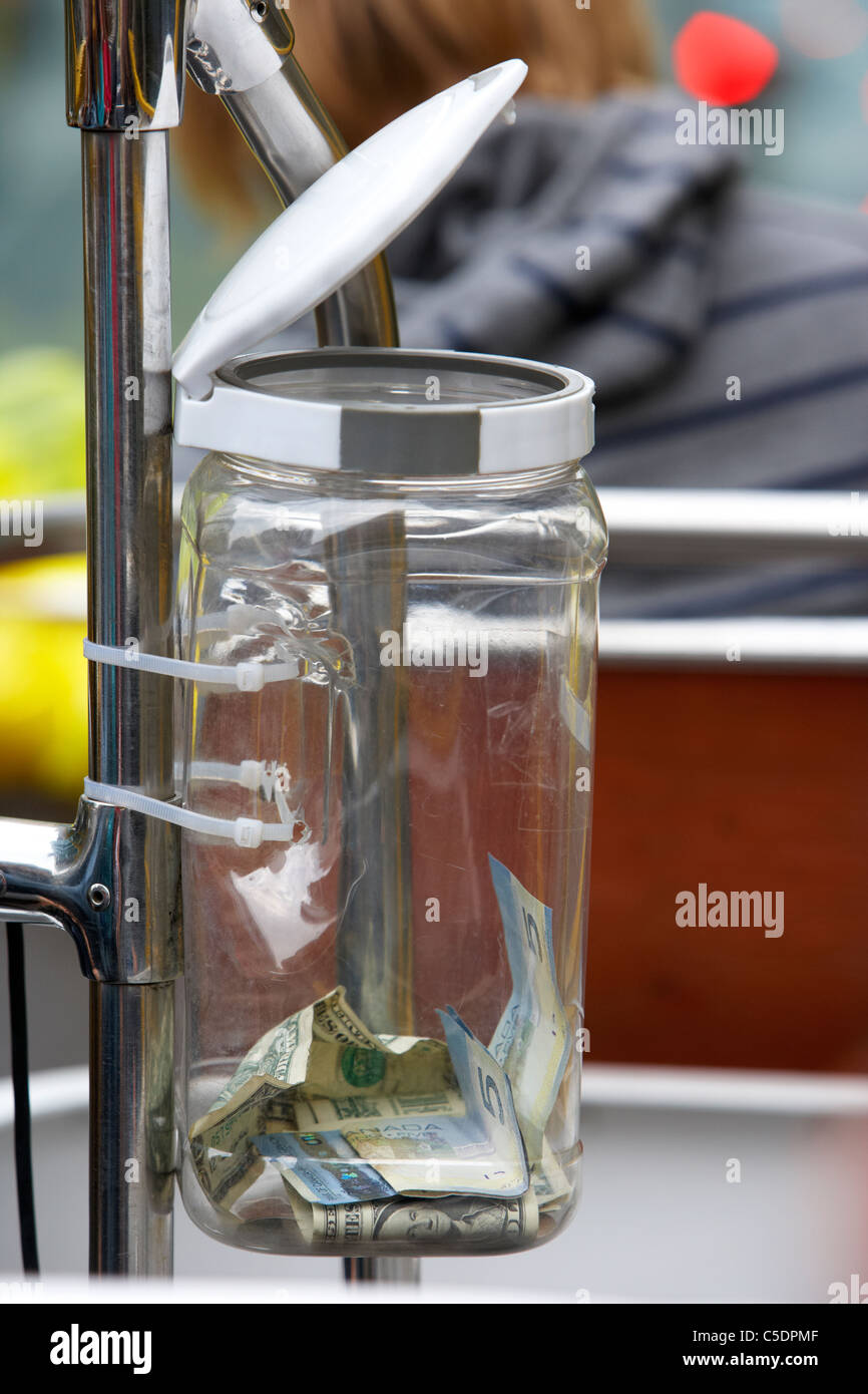 tips jar on a tour bus with us and candian money toronto ontario canada - Stock Image