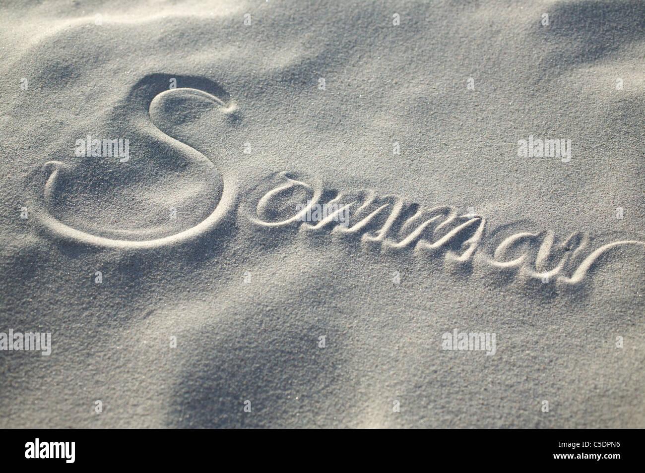 Close-up of summer written on sandy beach - Stock Image