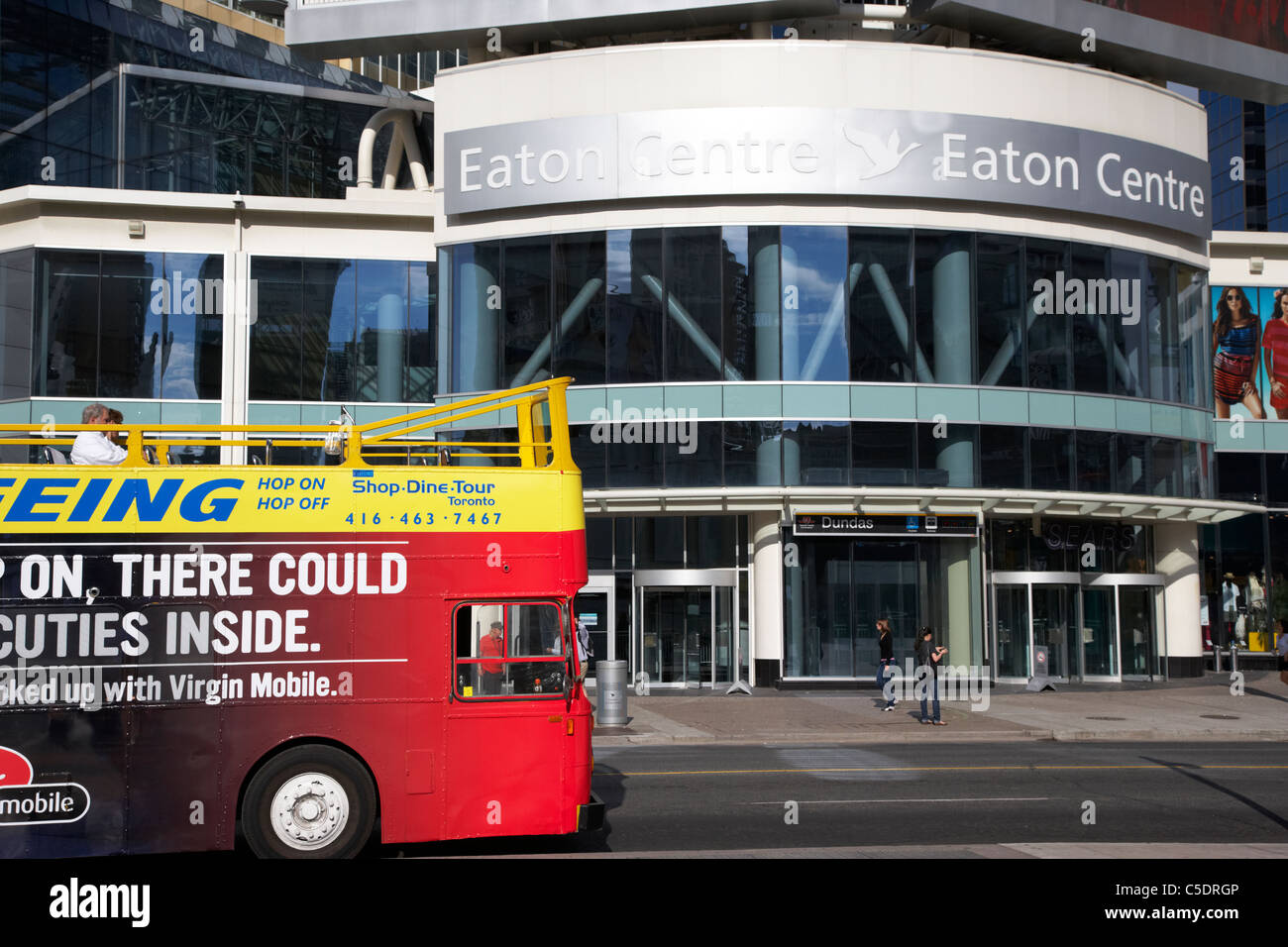 shop dine tour city sightseeing bus outside eaton centre in yonge dundas square toronto ontario canada - Stock Image