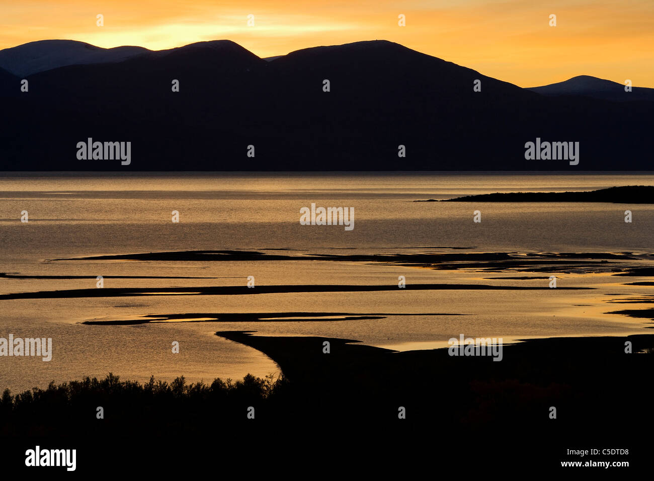 Beautiful view of silhouette mountains across the swamp at dusk - Stock Image