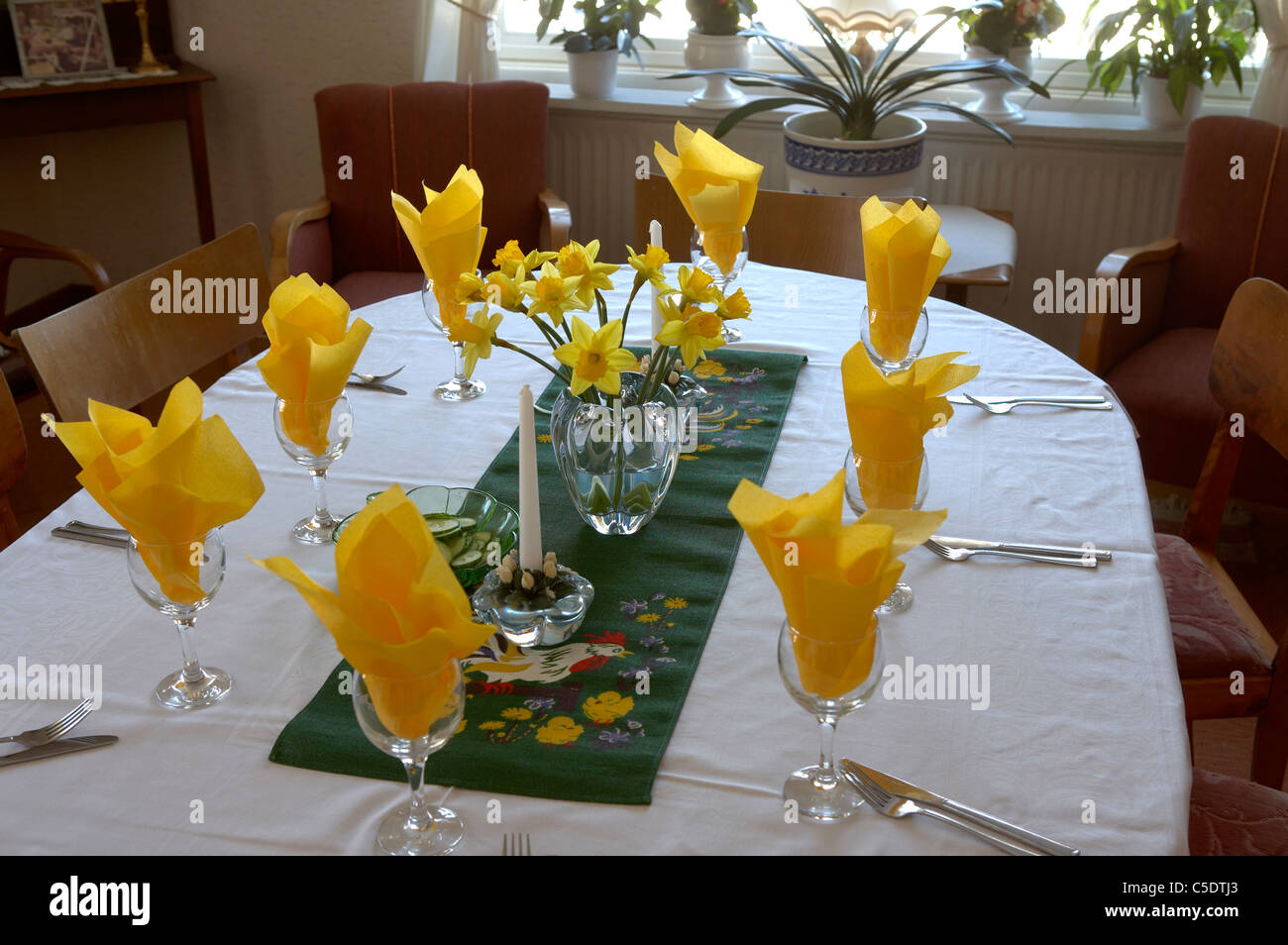 Close-up of set Easter dinner table with yellow napkins in glasses - Stock Image