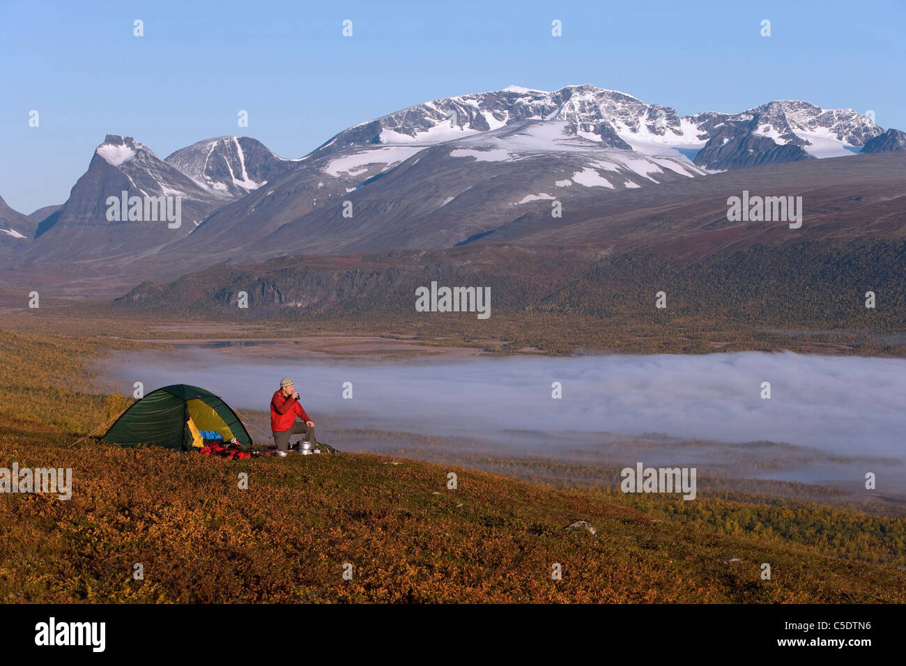 Hiker by tent and fog on landscape with Kebnekaise in the background at Lapland, Sweden - Stock Image