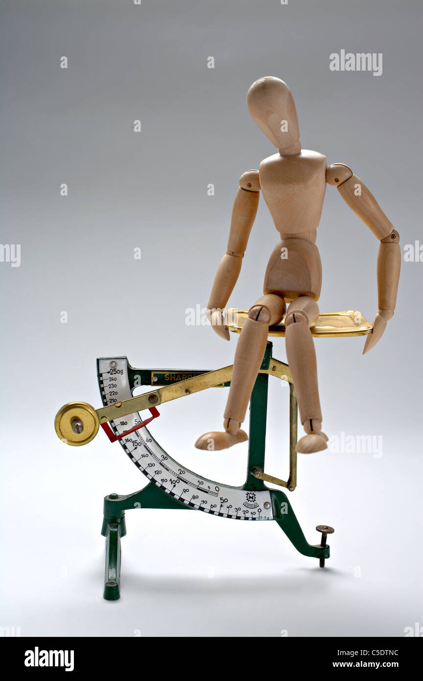 Mannequin sitting on weight scale against gray background - Stock Image