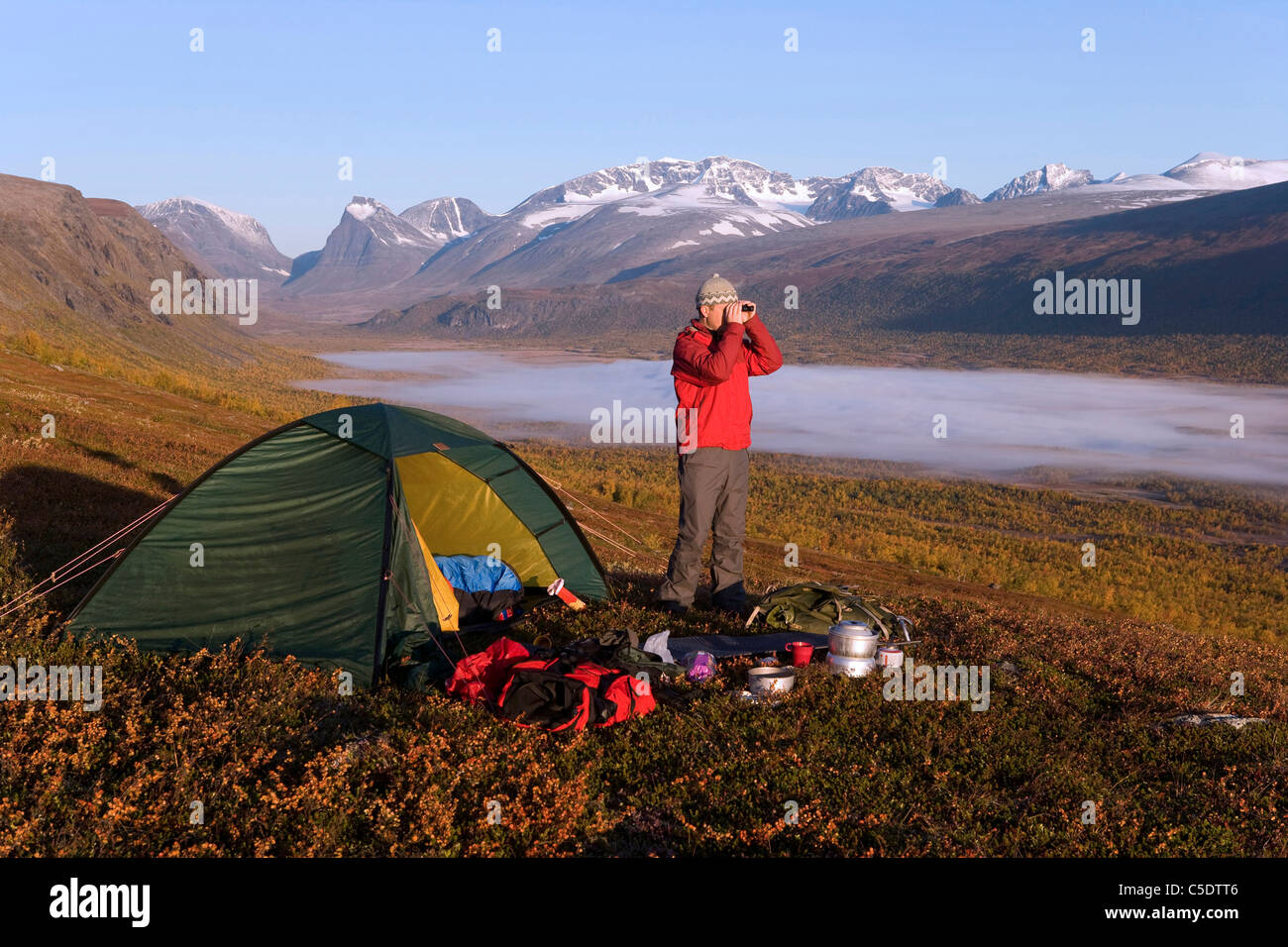 Hiker with binoculars by tent and fog on landscape with Kebnekaise against sky at Lapland, Sweden - Stock Image