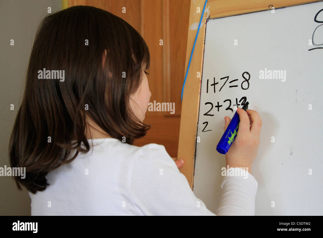 Young girl writing sums on a board - Stock Image