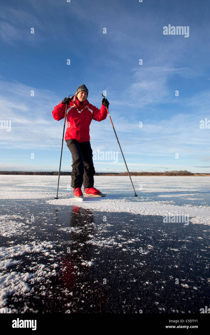 Full length of a woman with skates on frozen lake against the sky - Stock Image