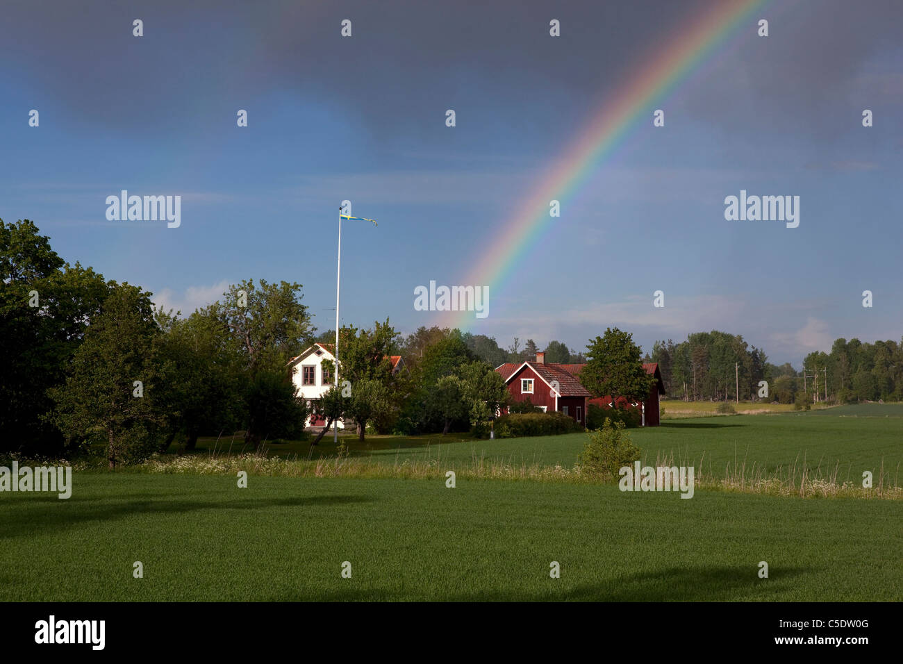 Rainbow behind country houses and trees with fields in foreground - Stock Image