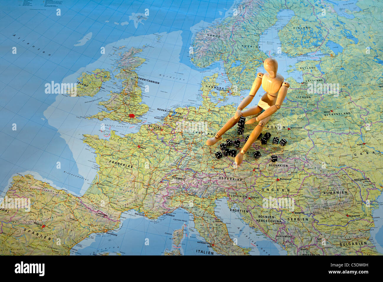 Close-up of a mannequin sitting on the map - Stock Image