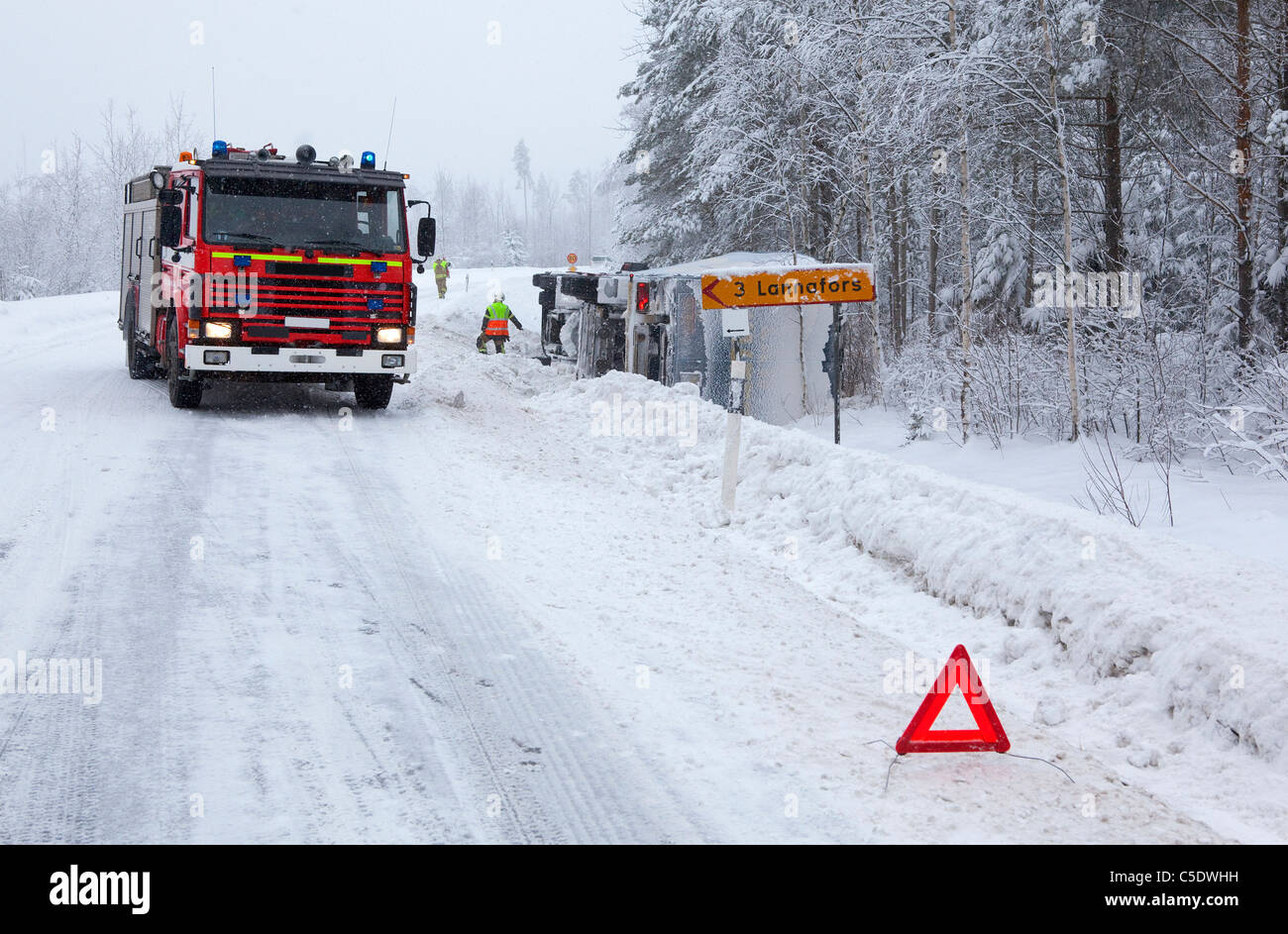 Fire brigade by a vehicle in ditch on winter road with warning sign in foreground - Stock Image