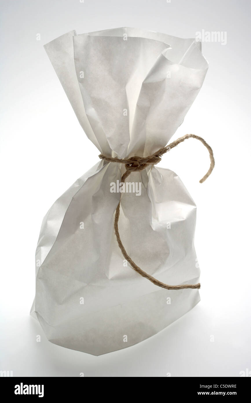 Close-up of a tied paper bag against white background - Stock Image