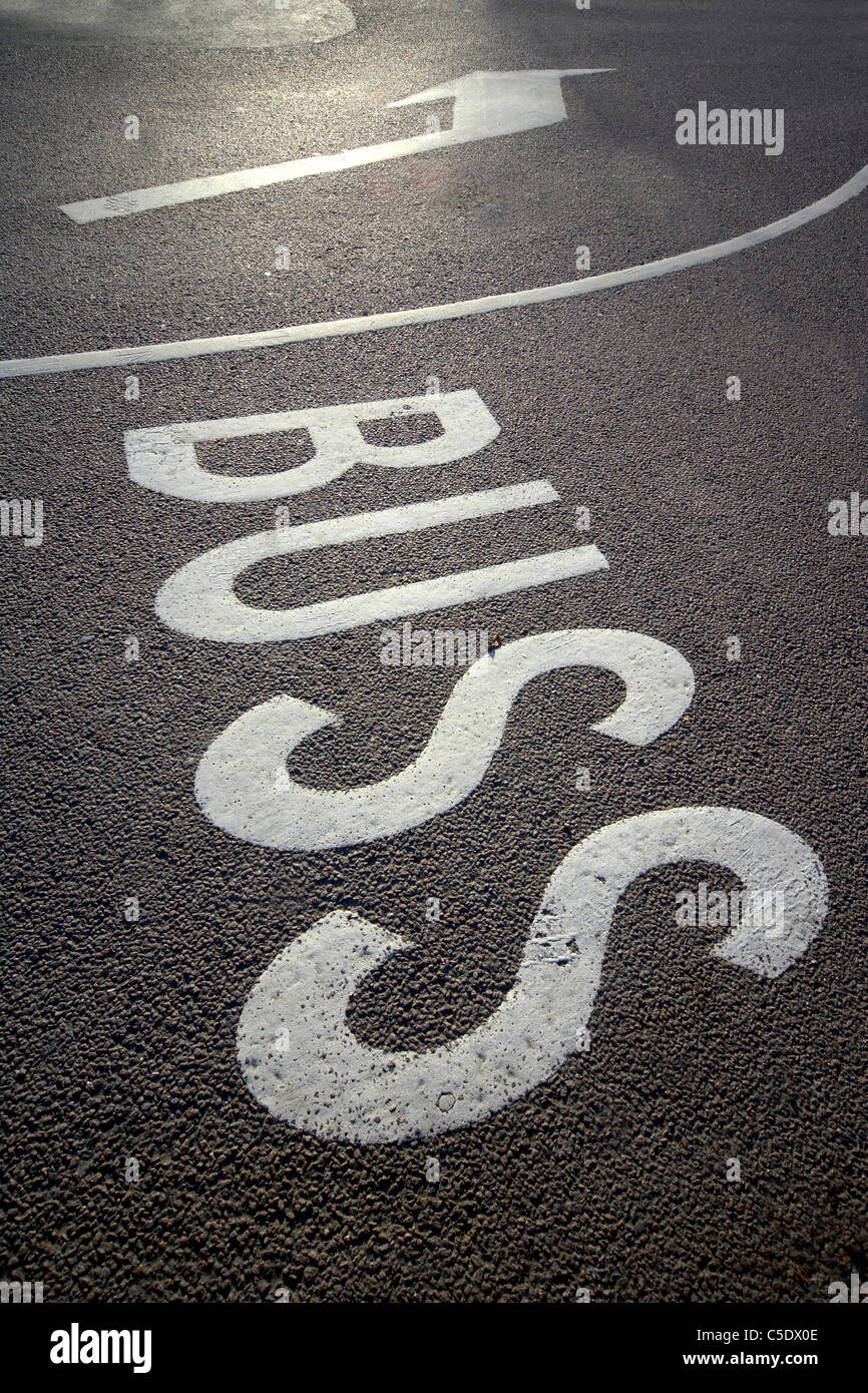 Close-up of road signs written on asphalt street - Stock Image