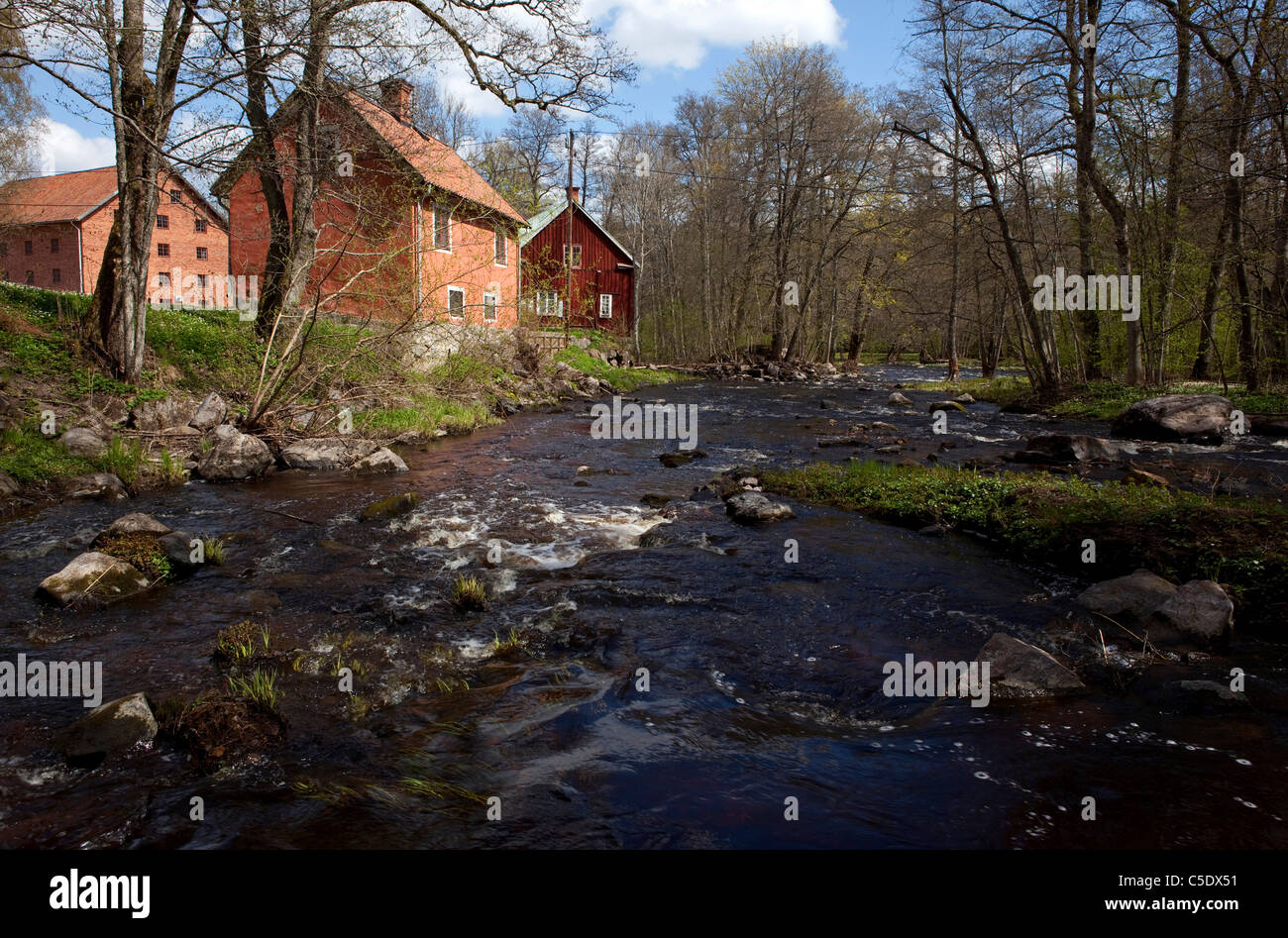 Svartån stream with country houses and bare trees in the background at Orebro, Sweden - Stock Image