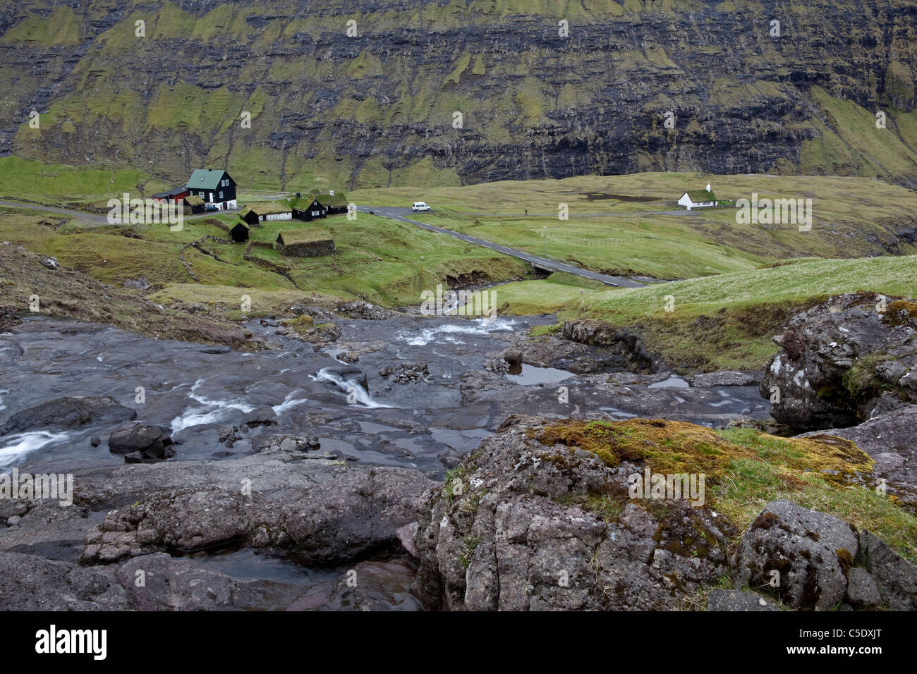 High angle view of country houses at a distance with rock stream in foreground at Faroe Islands - Stock Image