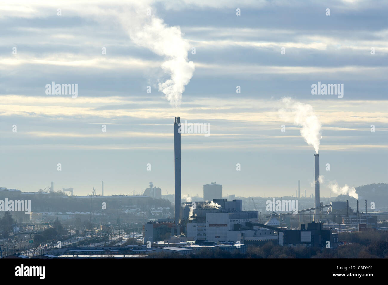 Chimneys emitting smoke at the industrial area against the sky Stock Photo