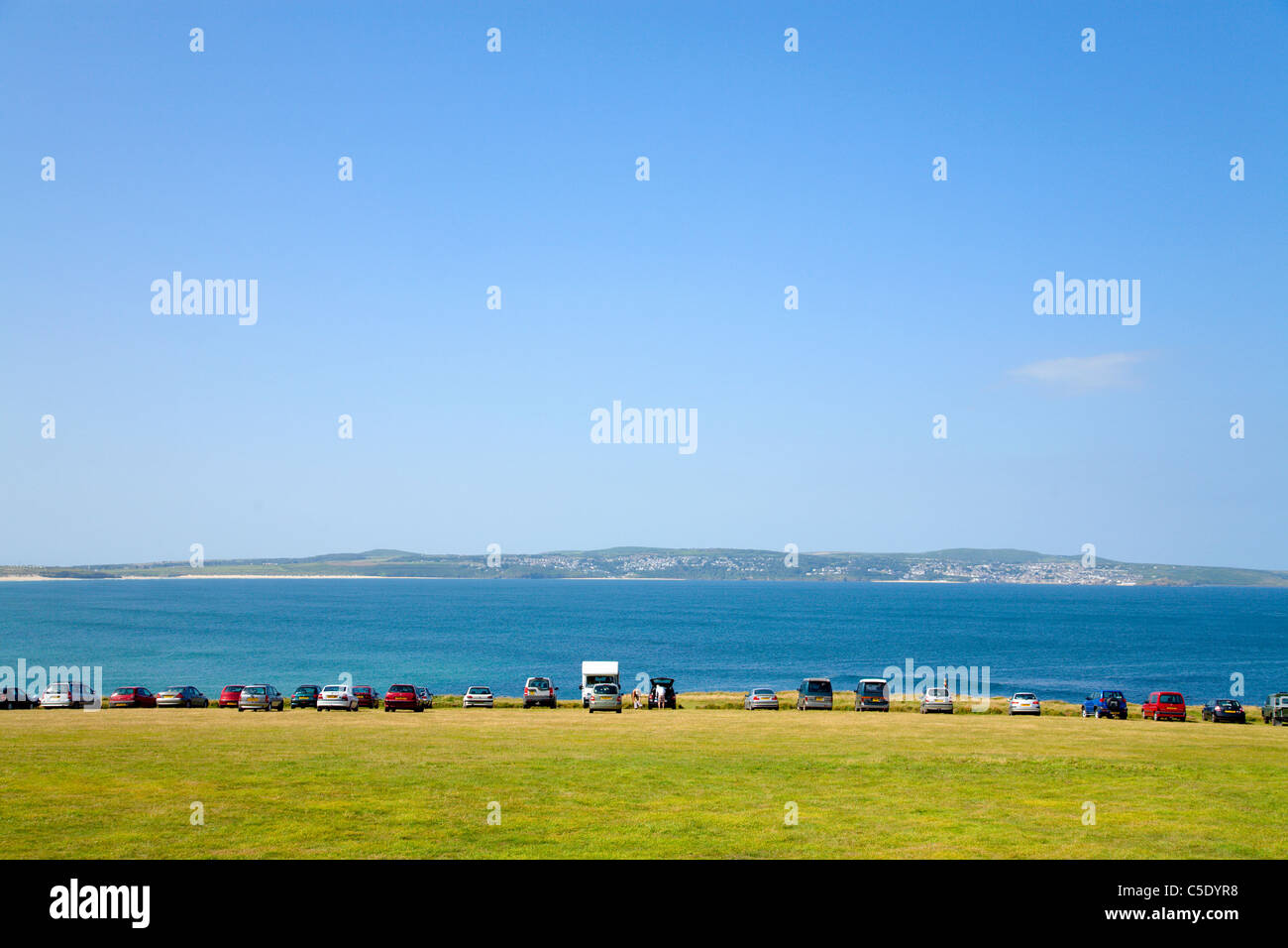 Mid distance shot of parked cars at St Ives Bay with landscape in the foreground - Stock Image