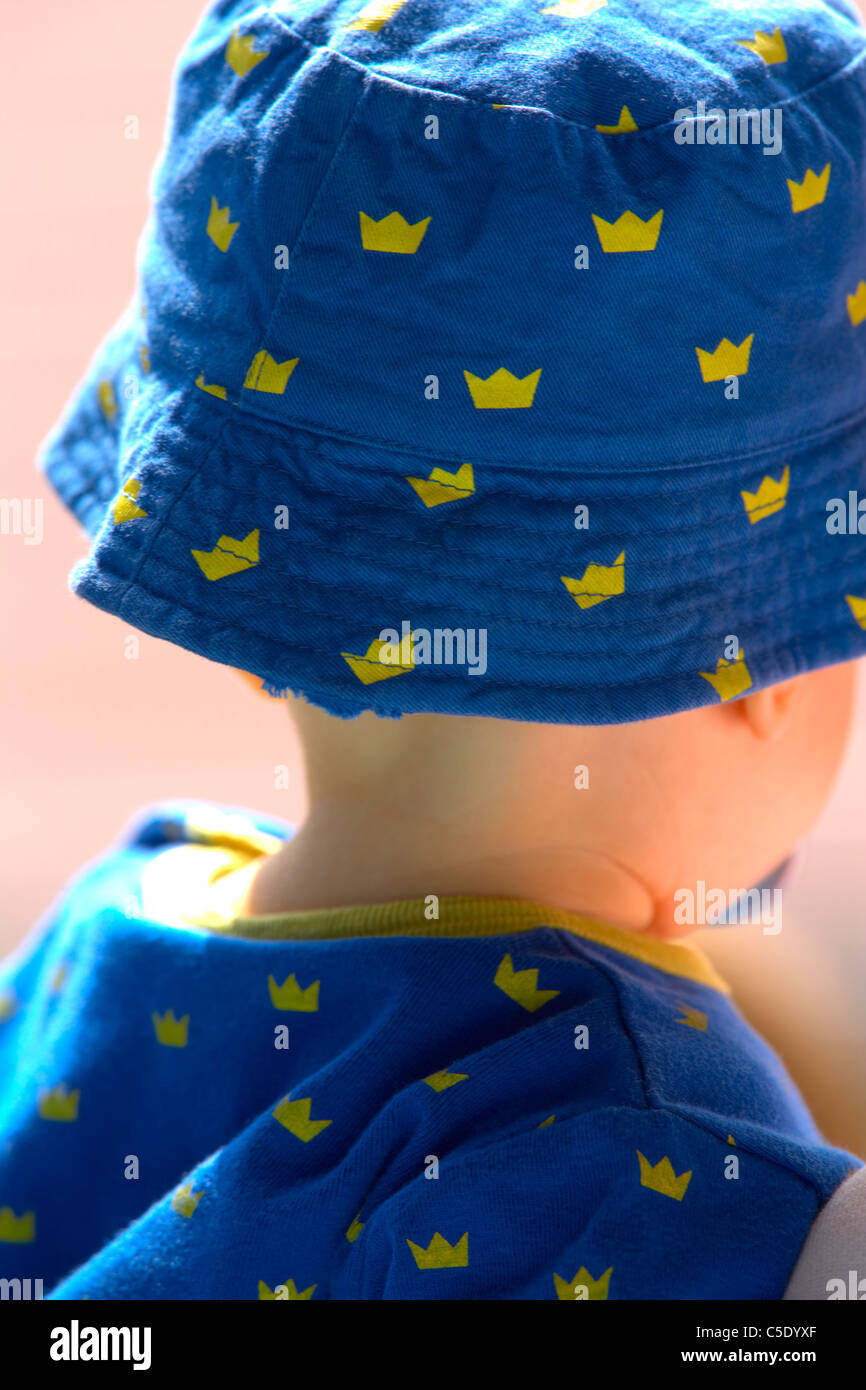 Close-up rear view of a little kid in Sweden Supporter cap and dress - Stock Image