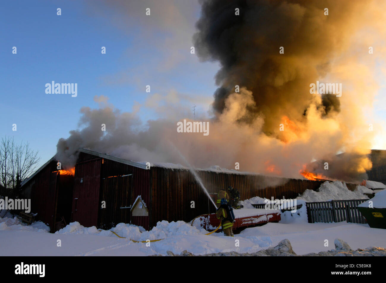 House fire being extinguish against blue sky in winter - Stock Image