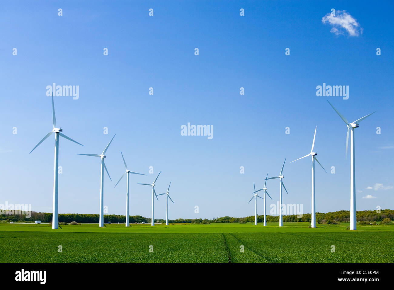 Group of wind turbines at peaceful fields against blue sky - Stock Image