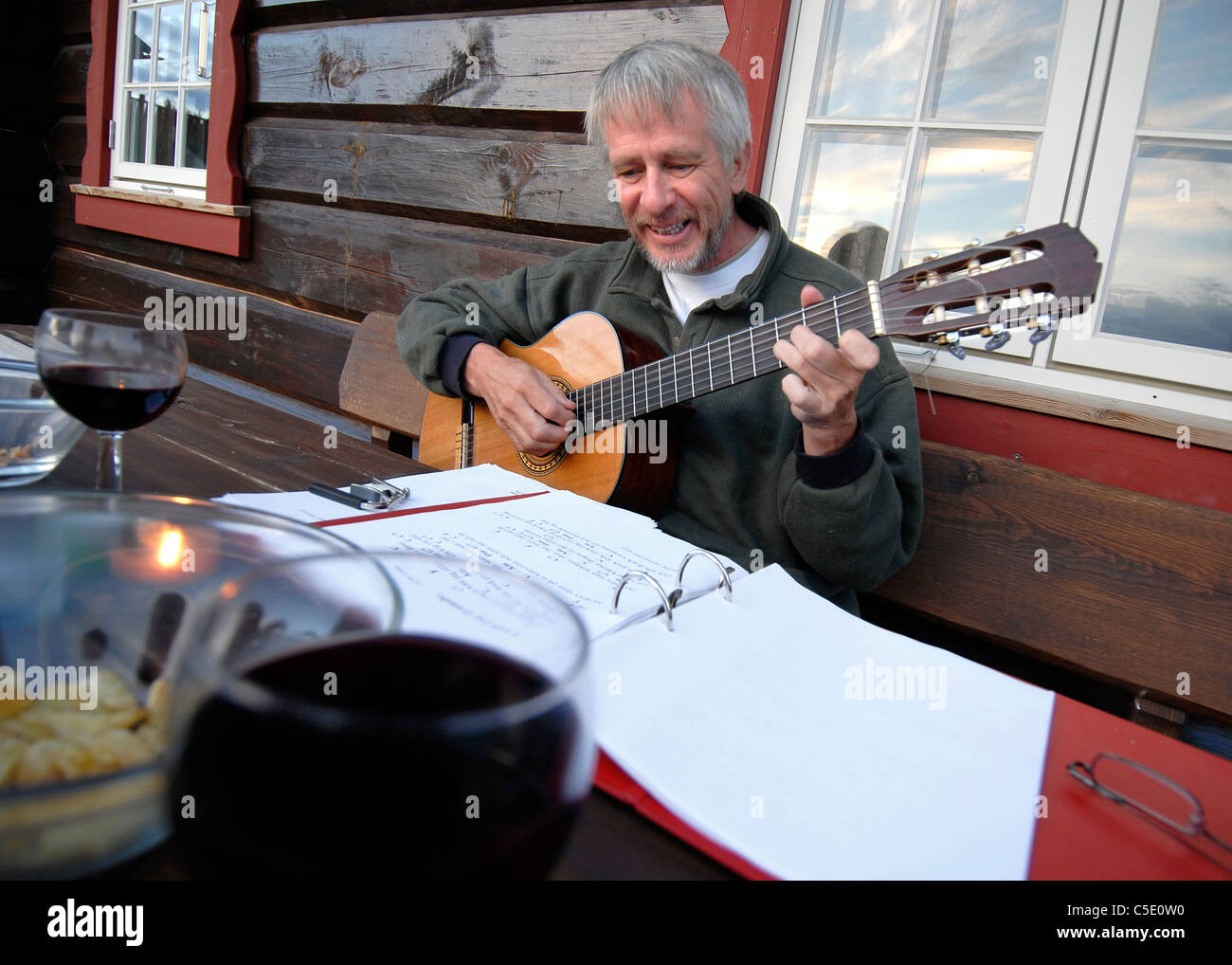 Middle-aged man playing the guitar at dining table - Stock Image