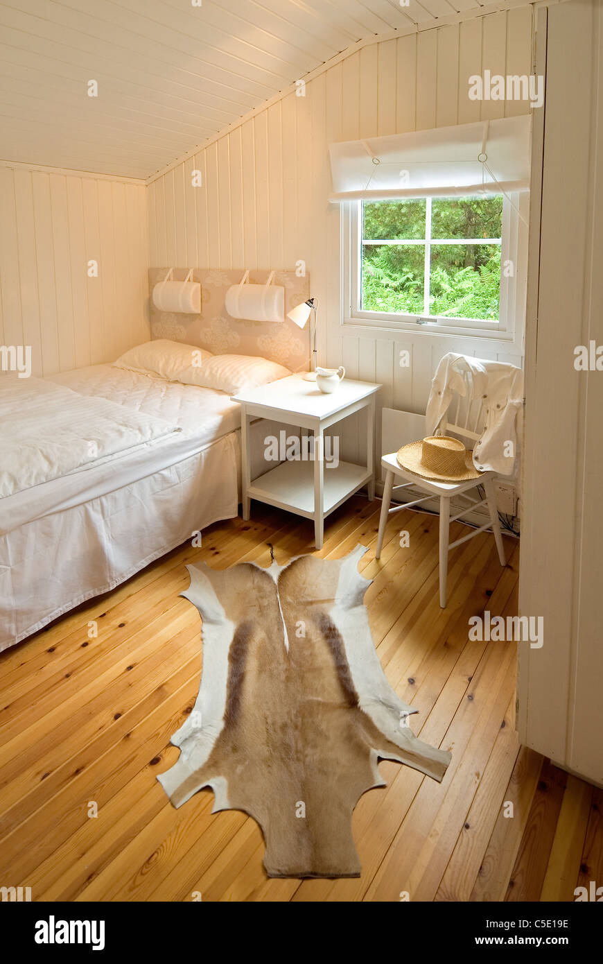 View of a window by bed with animal skin rug on wooden floor at a bedroom in house - Stock Image