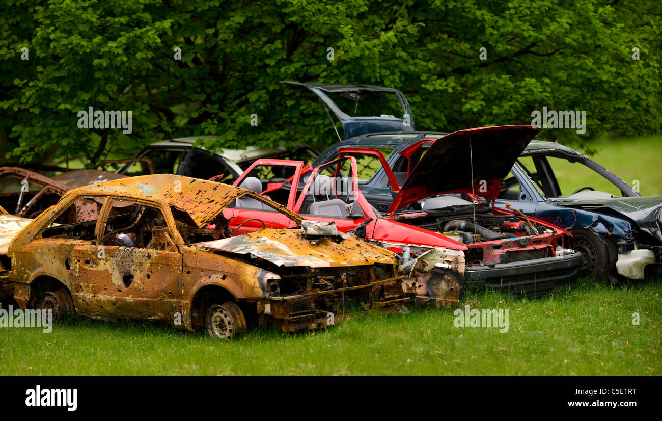 Deformed abandoned cars on grass and against the trees - Stock Image