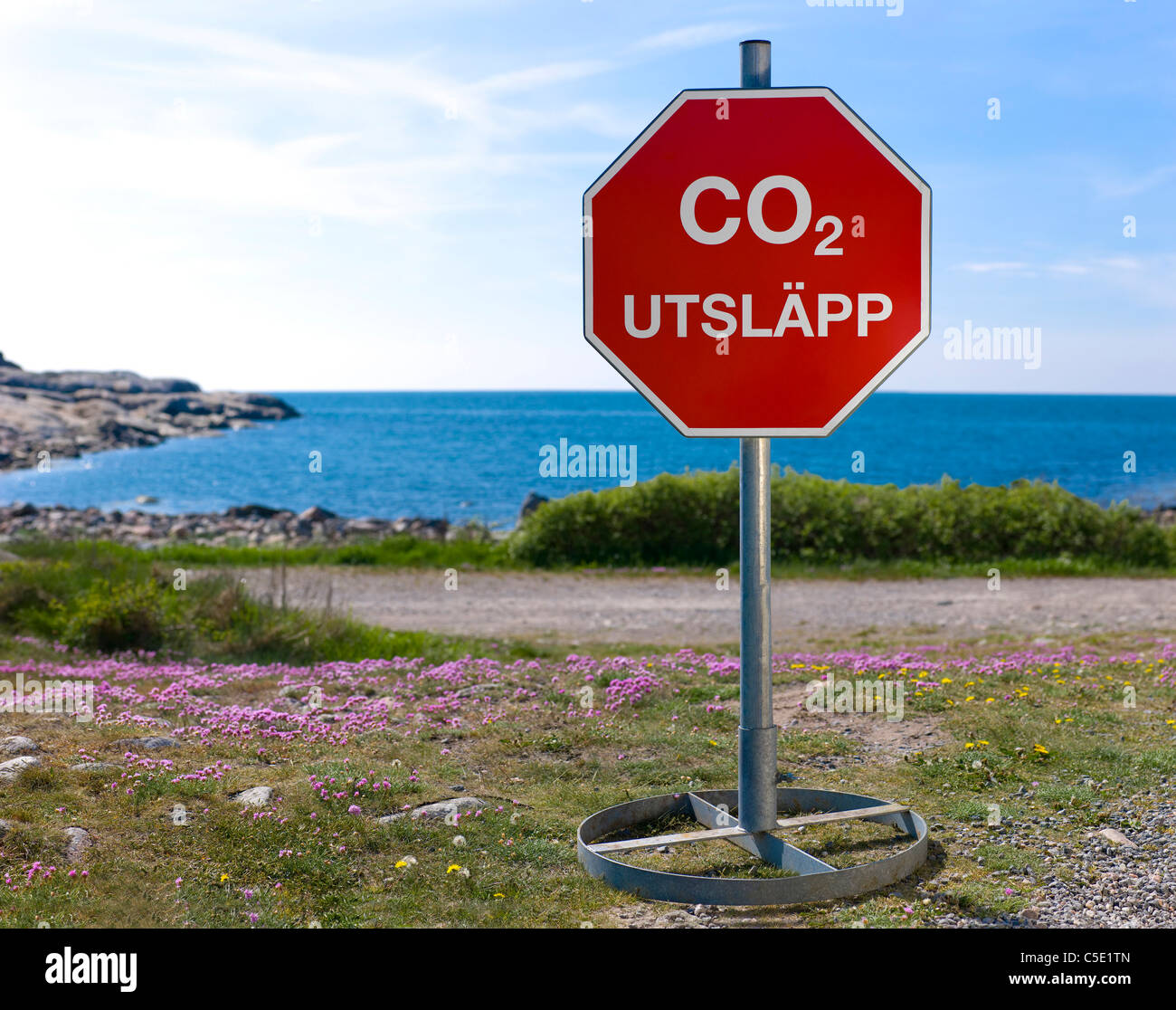CO2 emissions signpost in front of the blue sky - Stock Image