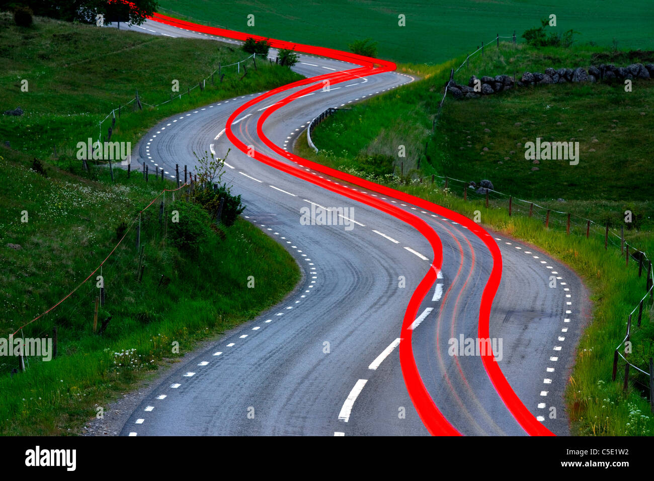 Red tail lights along the winding country road and fields - Stock Image