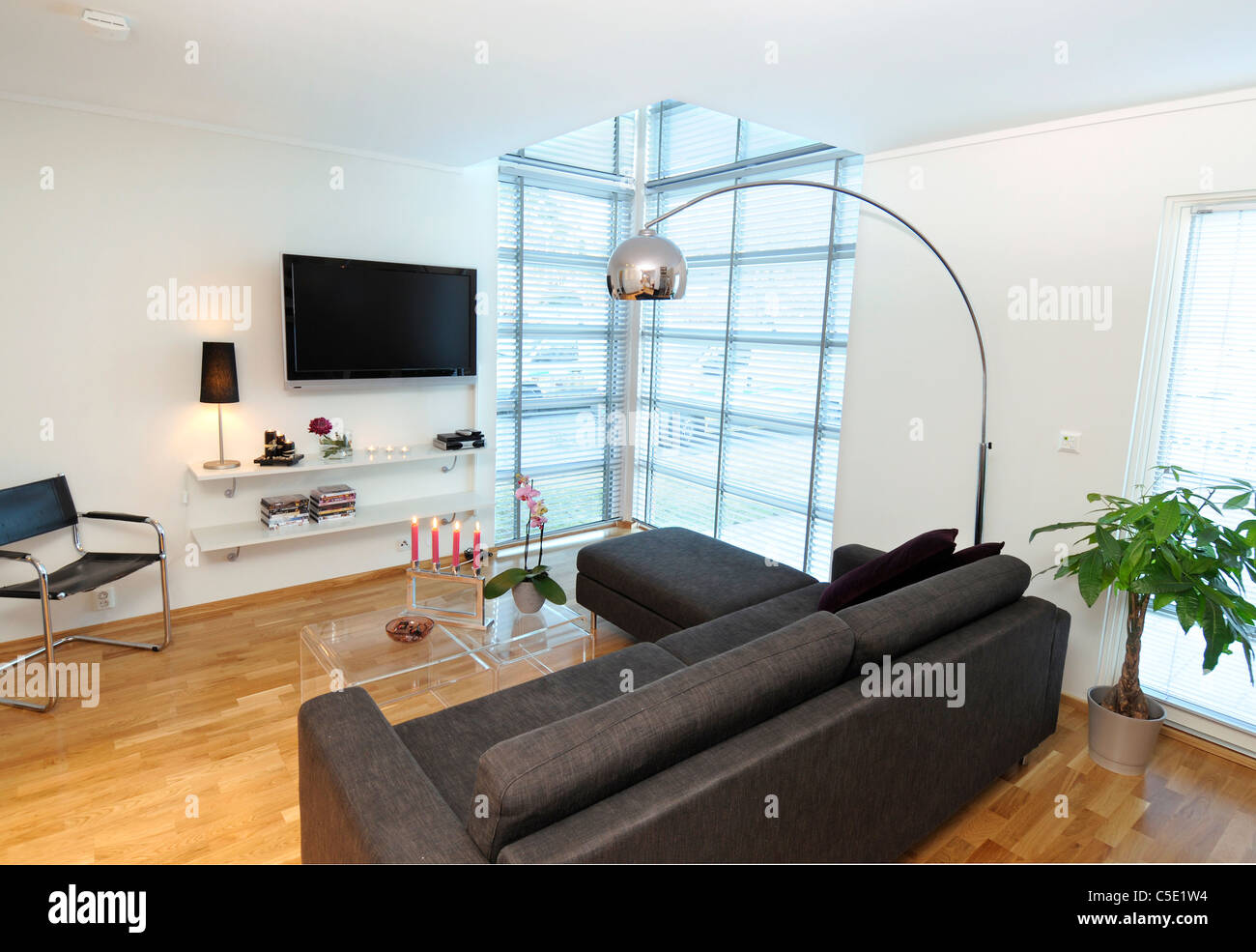 View of floor lamp over black sofa set with flat screen TV ...