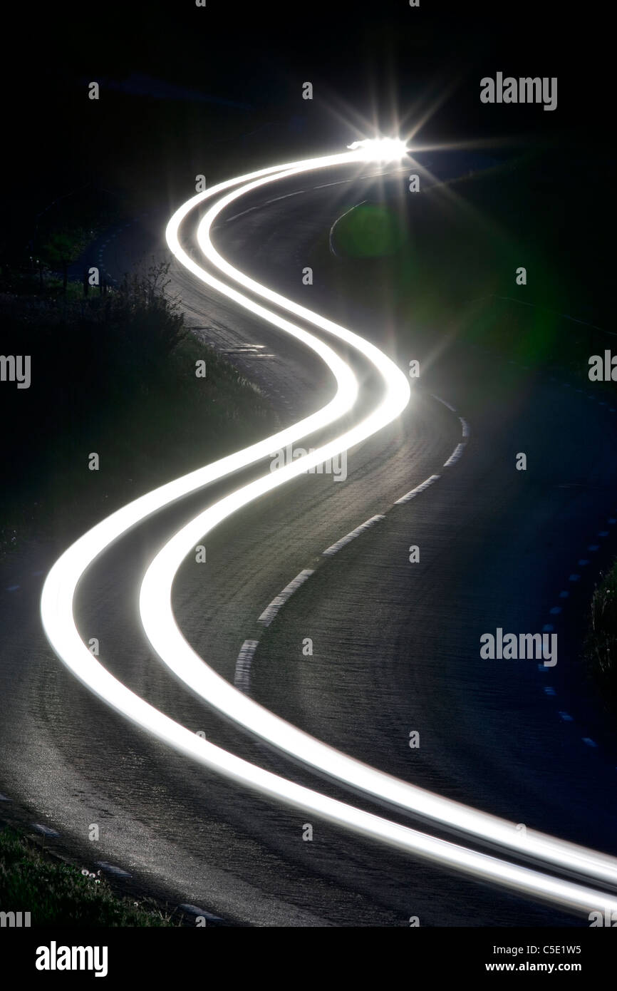 Tail lights along the winding country road at night - Stock Image