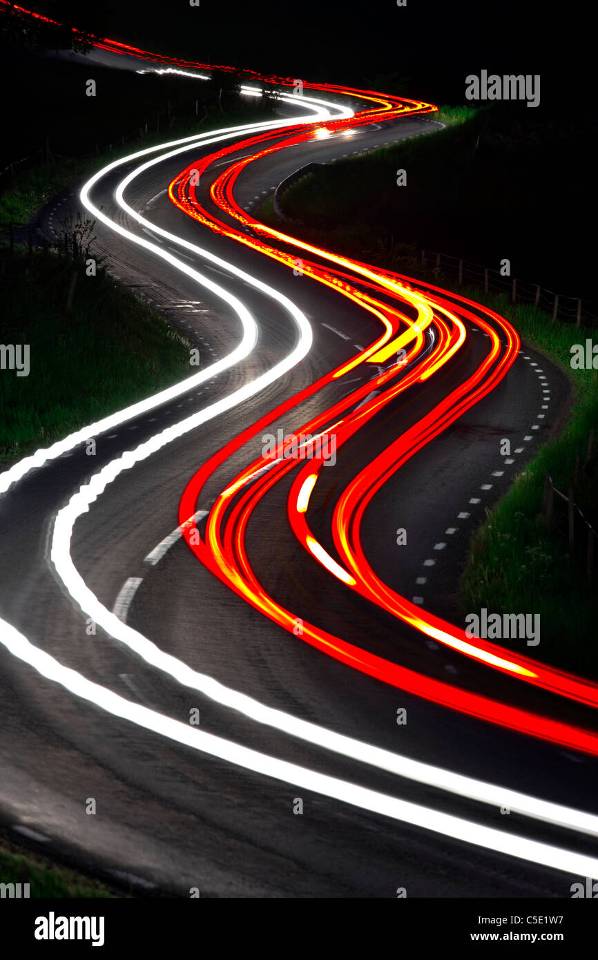 Red tail lights along the winding country road at night - Stock Image