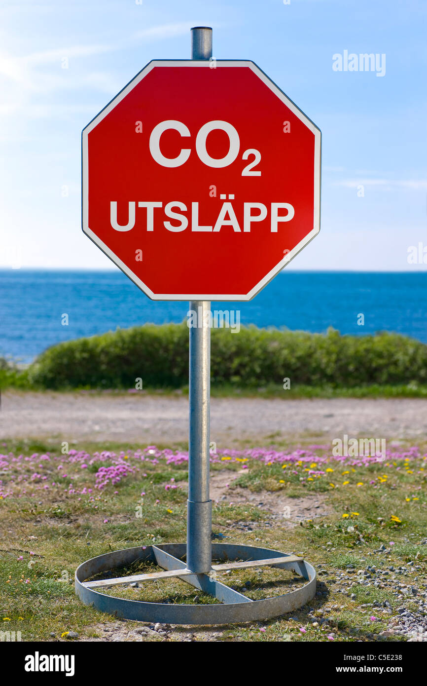 CO2 emission signpost with blue sea in the background - Stock Image