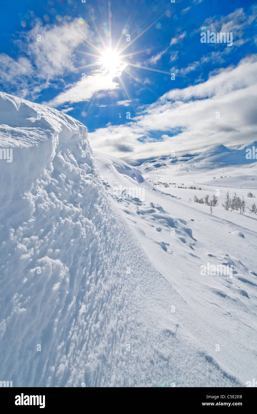 Low angle view of the sun shining over the snowed mountain top with blue sky and clouds - Stock Image