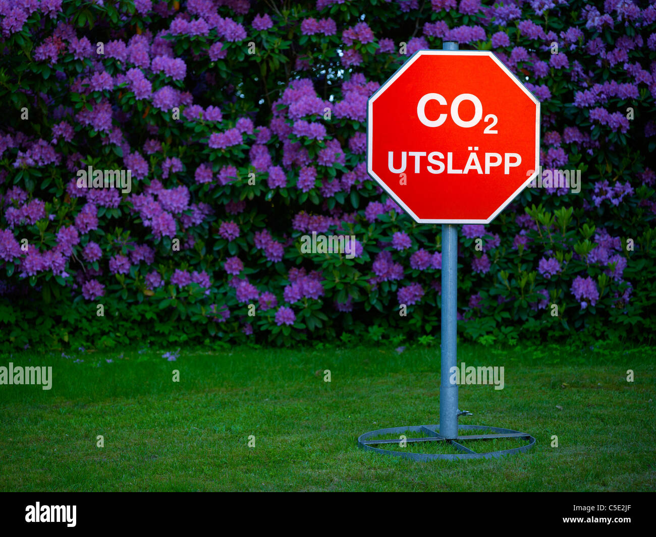 CO2 emission signpost on grass against flowers - Stock Image