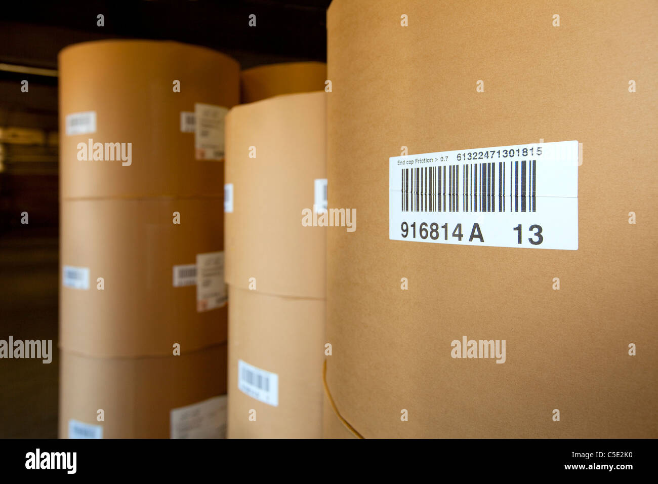 Close-up of stocked large paper rolls with bar codes - Stock Image