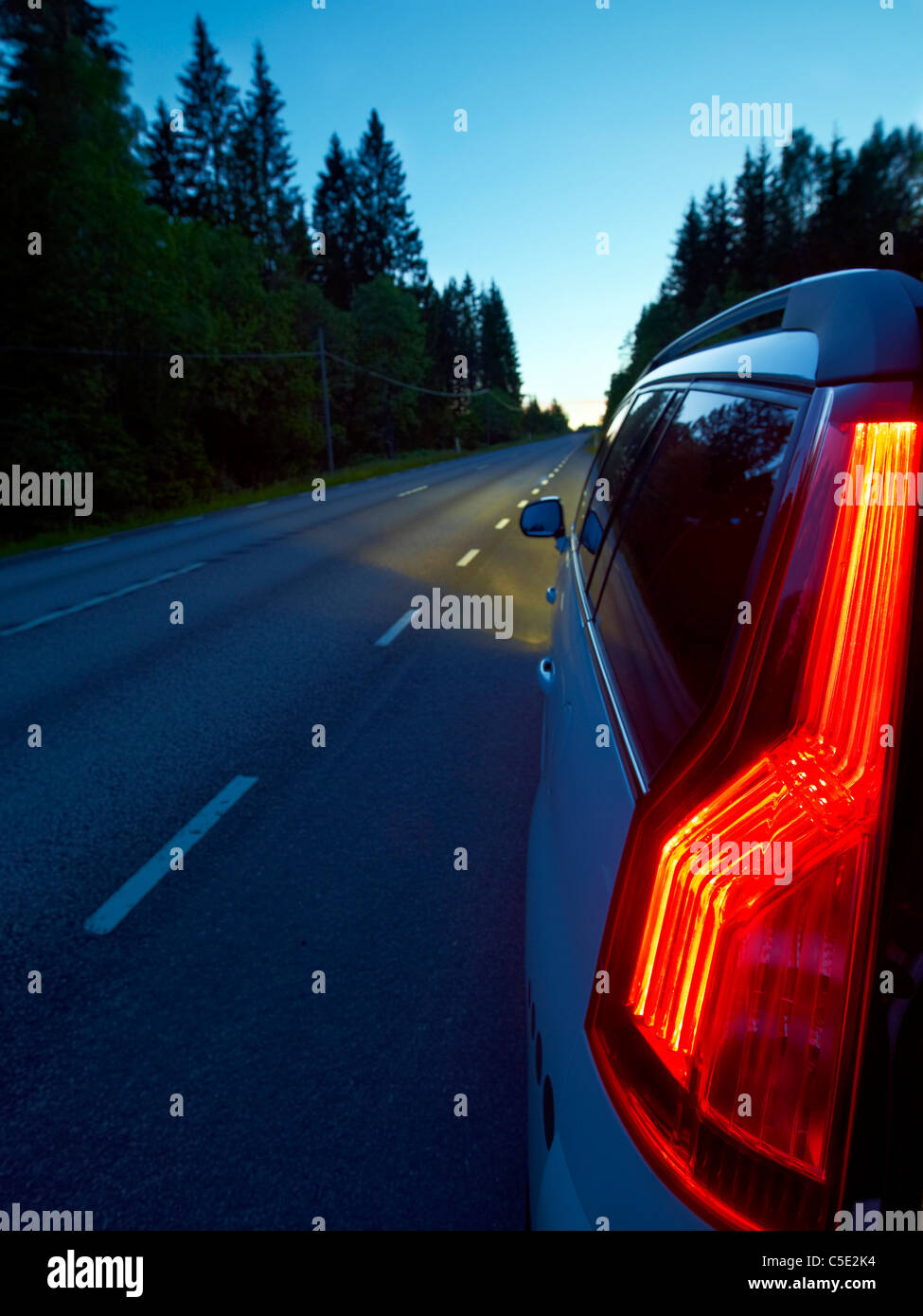 Close-up of tail lights on the country road along trees at dusk - Stock Image