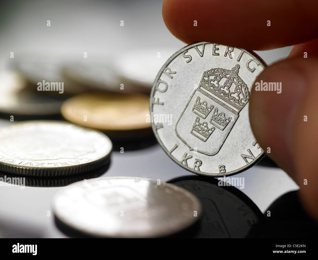 Close-up of a hand holding Swedish coin along the coins on table - Stock Image