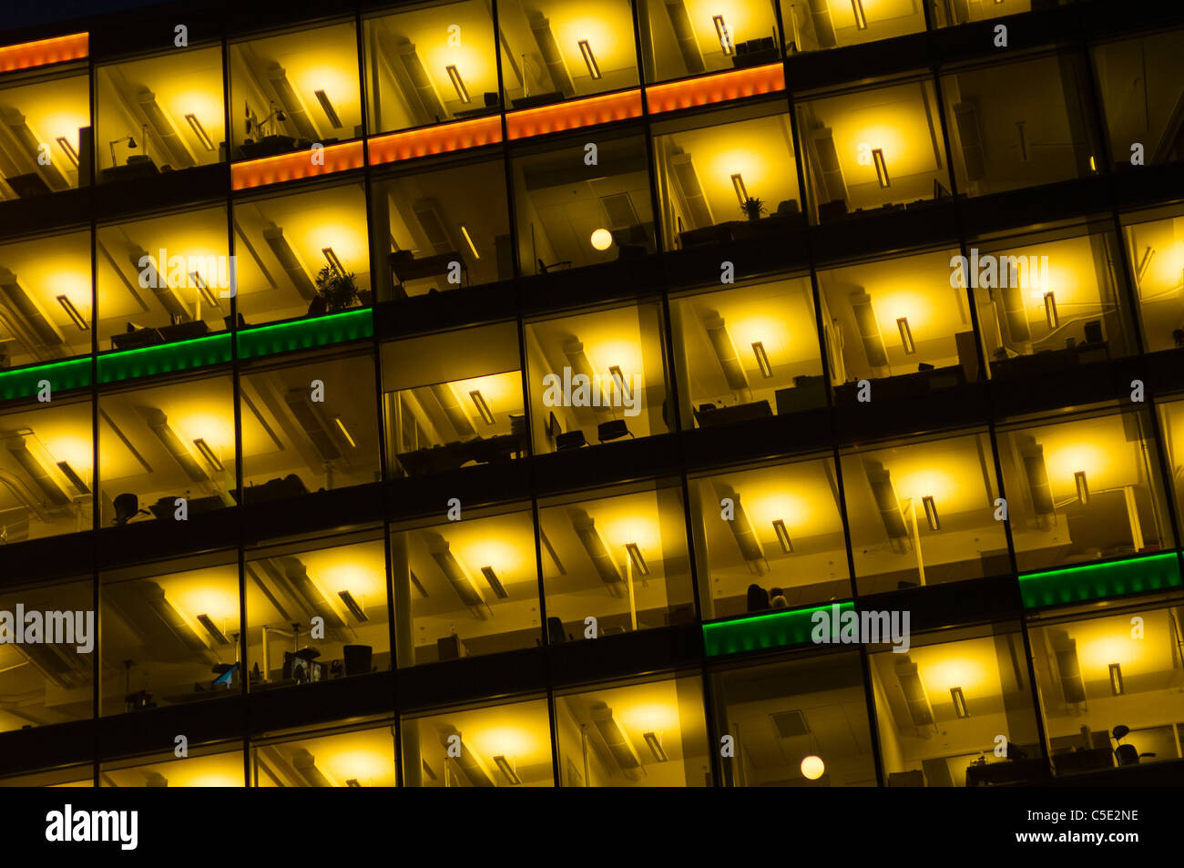 Low angle view of illuminated open-plan office building with windows - Stock Image